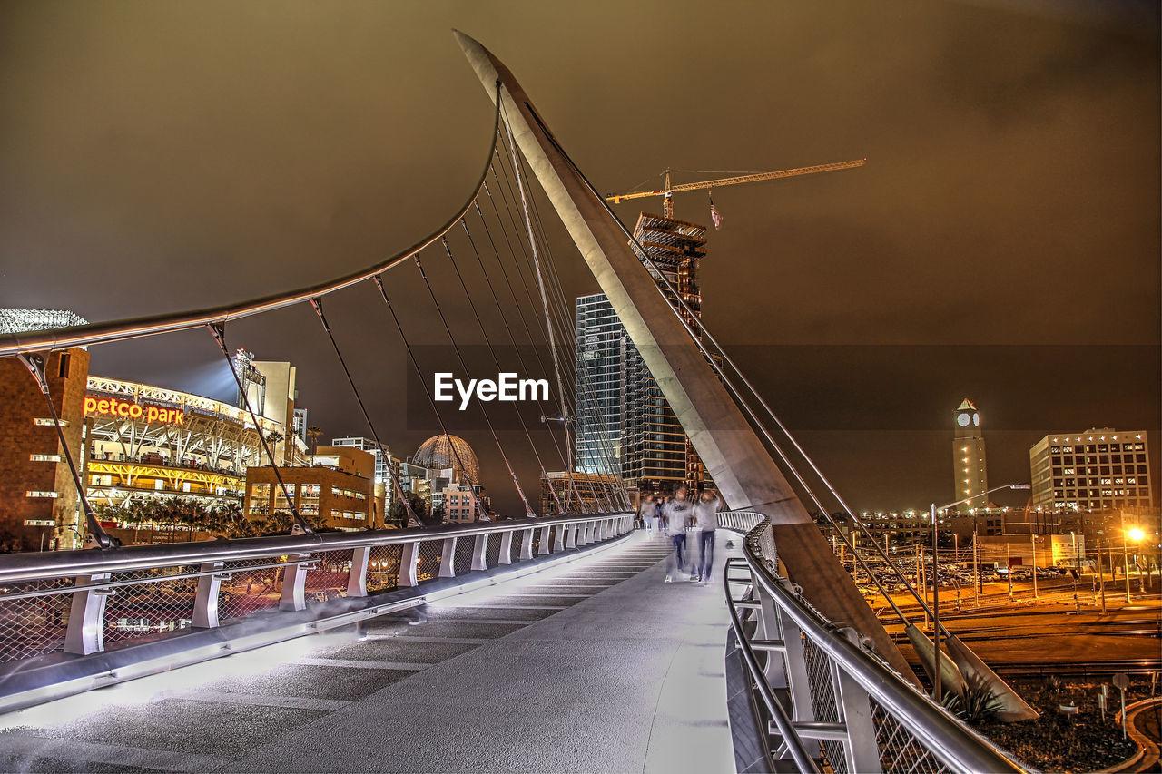 ILLUMINATED BRIDGE AND BUILDINGS AGAINST SKY
