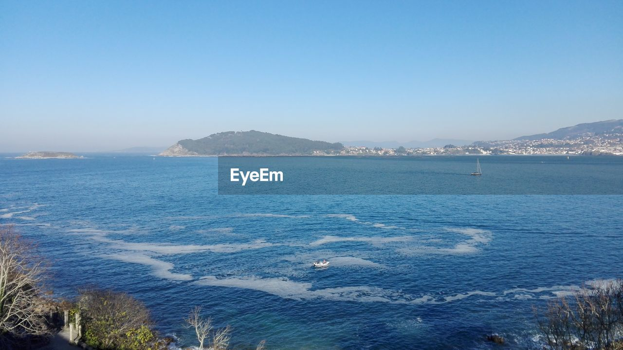 SCENIC VIEW OF SEA AND MOUNTAIN AGAINST CLEAR BLUE SKY