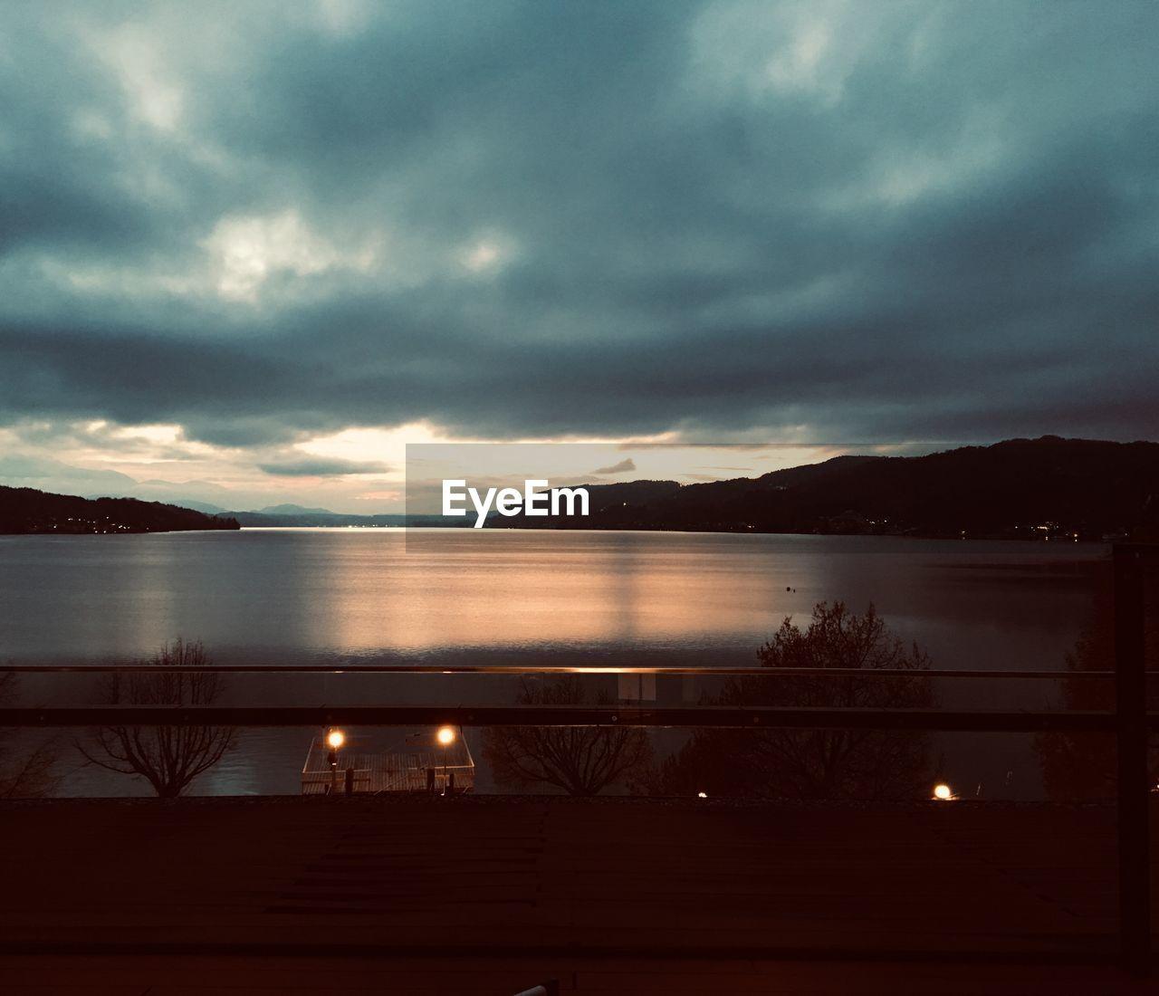 sky, water, cloud - sky, scenics - nature, beauty in nature, tranquil scene, tranquility, nature, no people, mountain, lake, reflection, overcast, illuminated, outdoors, dusk, idyllic