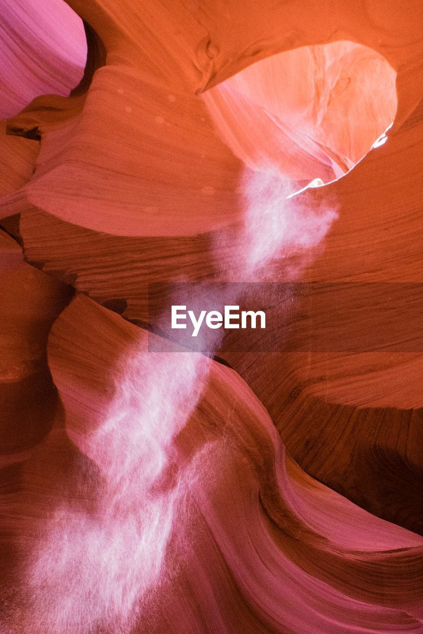 Low angle view of sunlight falling in slot canyon