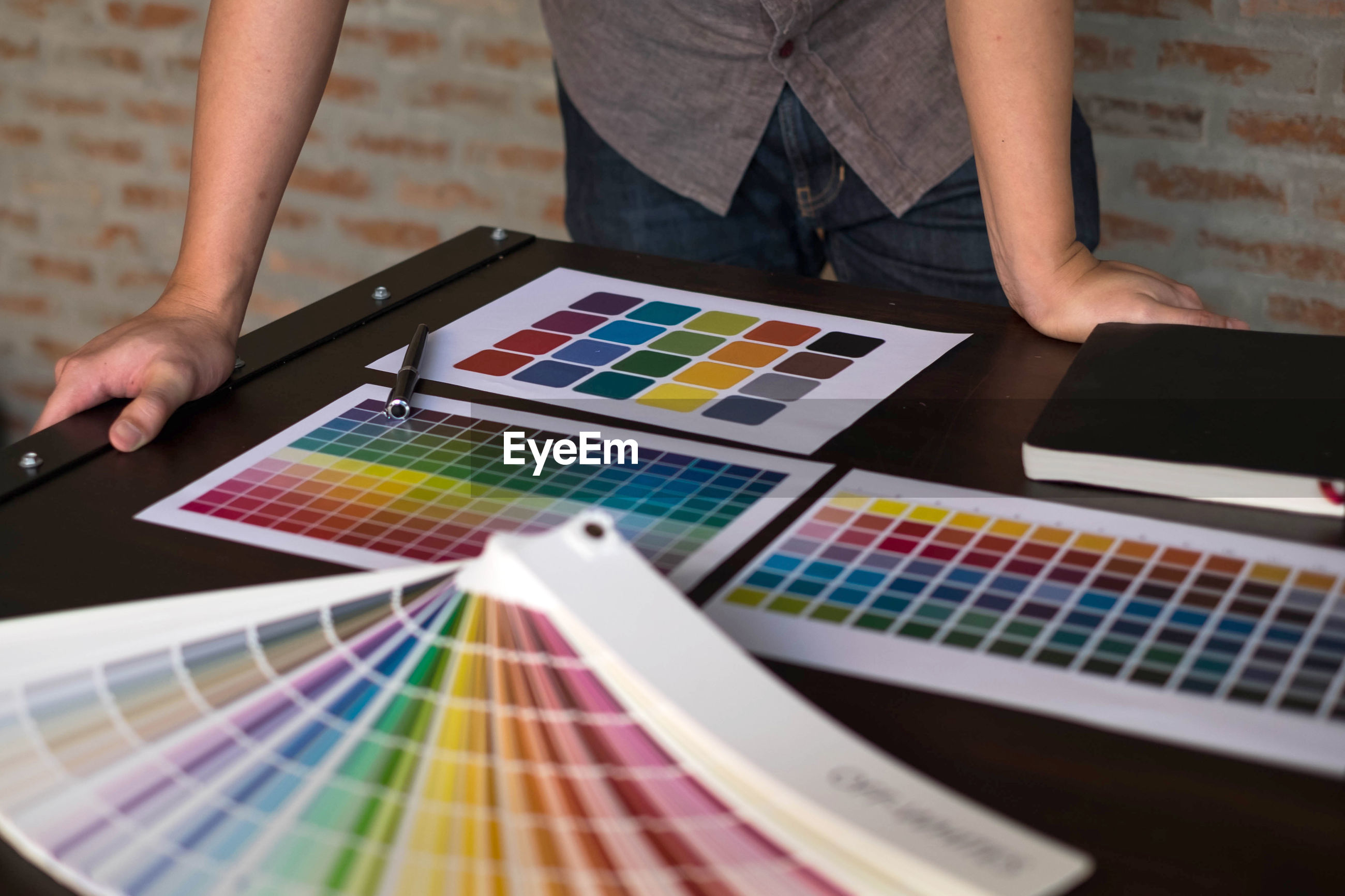 Midsection of design professional with color swatches on table