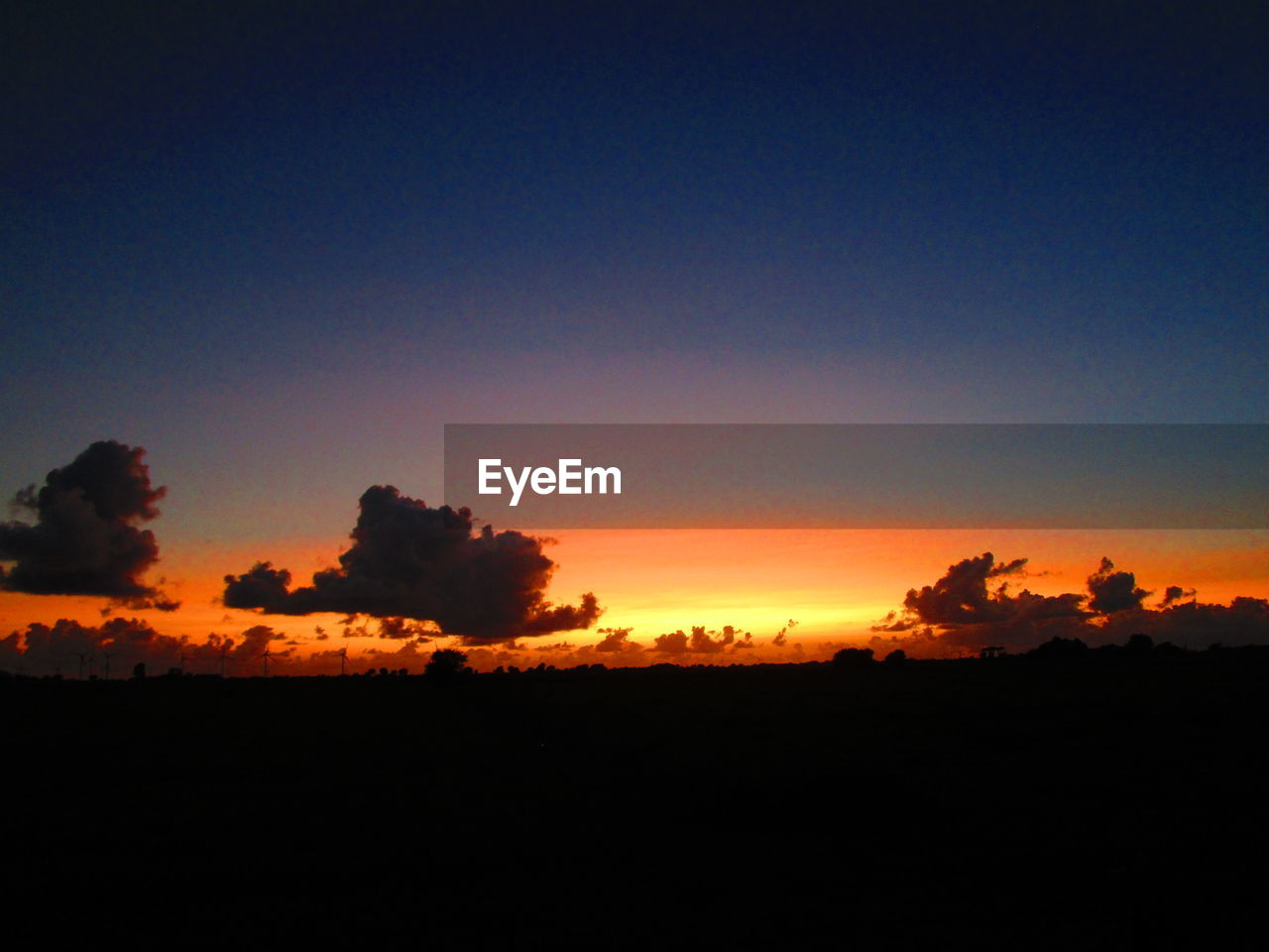 sky, sunset, beauty in nature, tranquility, silhouette, tranquil scene, scenics - nature, orange color, copy space, environment, nature, no people, cloud - sky, landscape, idyllic, outdoors, non-urban scene, dark, land, field