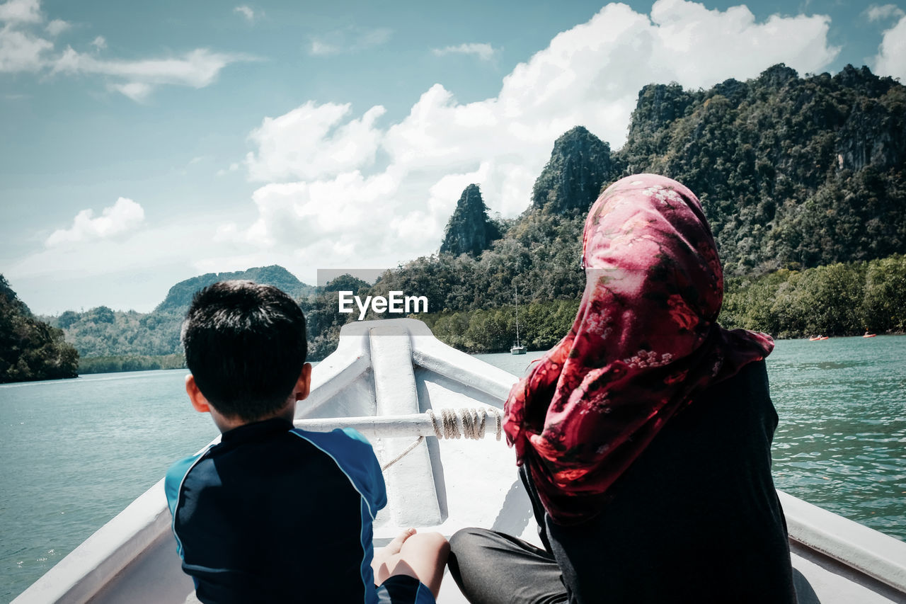 Rear View Of Siblings Sitting On Boat Sailing Against River