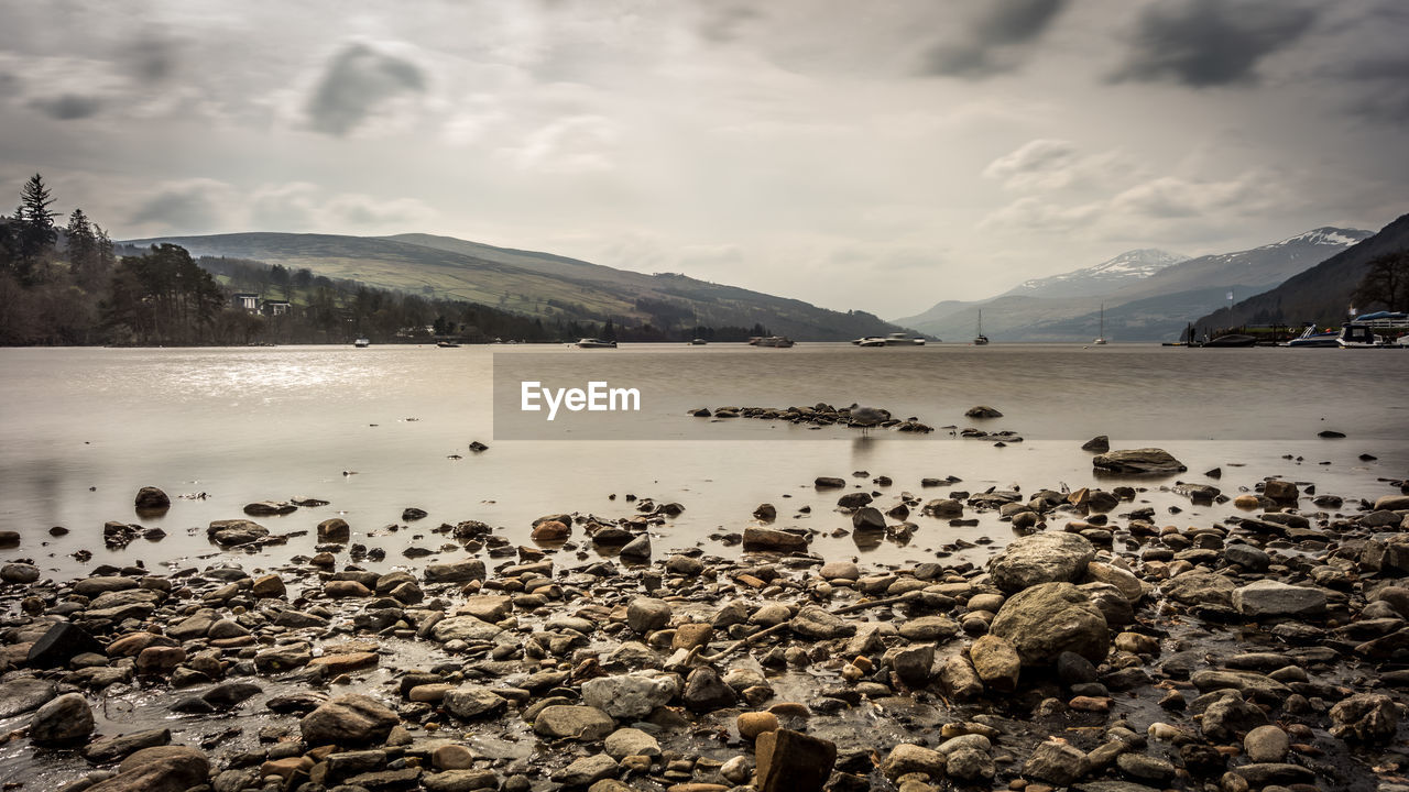water, mountain, cloud - sky, sky, beauty in nature, scenics - nature, tranquil scene, tranquility, rock, nature, no people, non-urban scene, solid, rock - object, beach, lake, mountain range, day, mountain peak