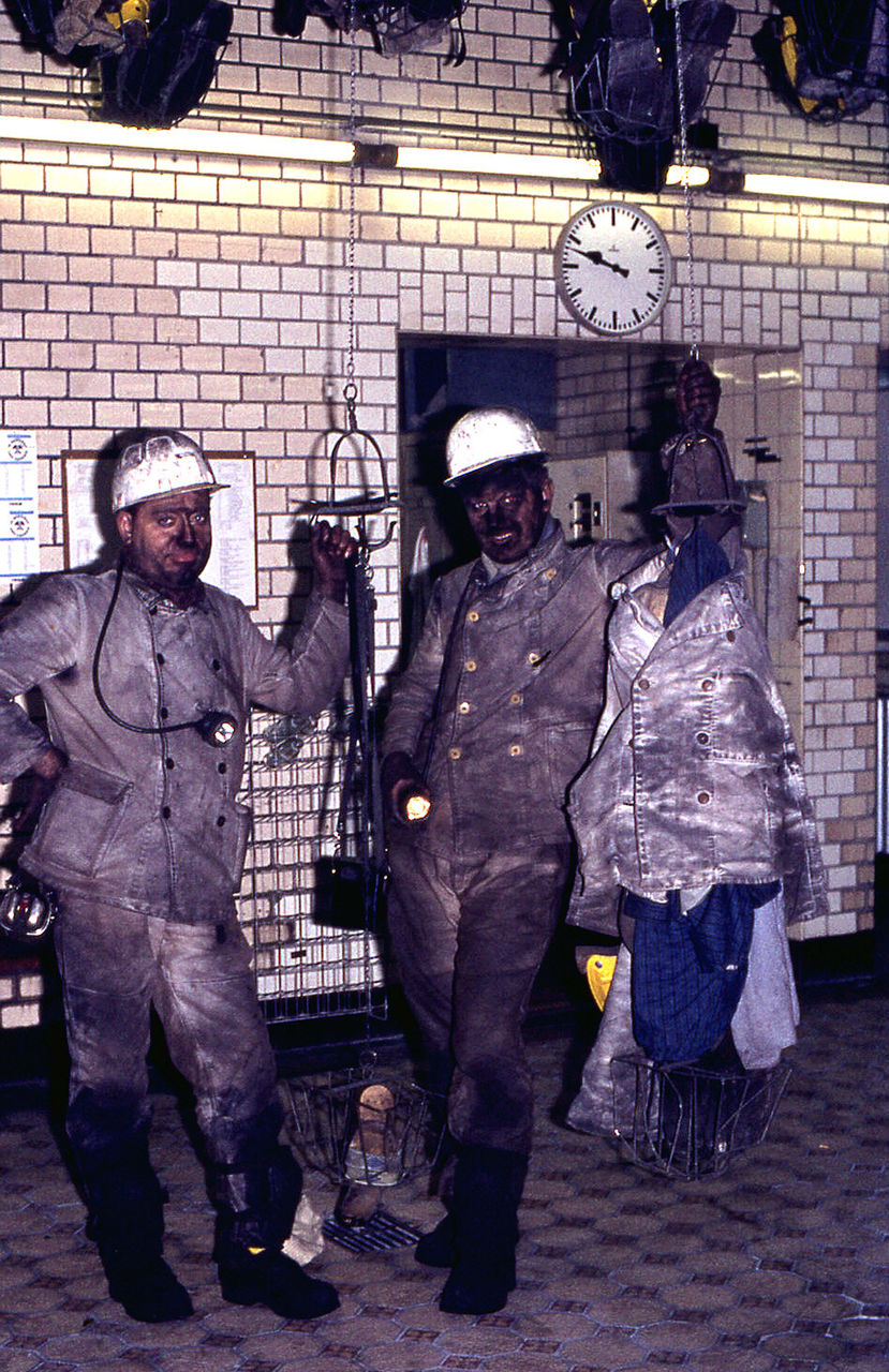 Portrait of miners standing against factory at night