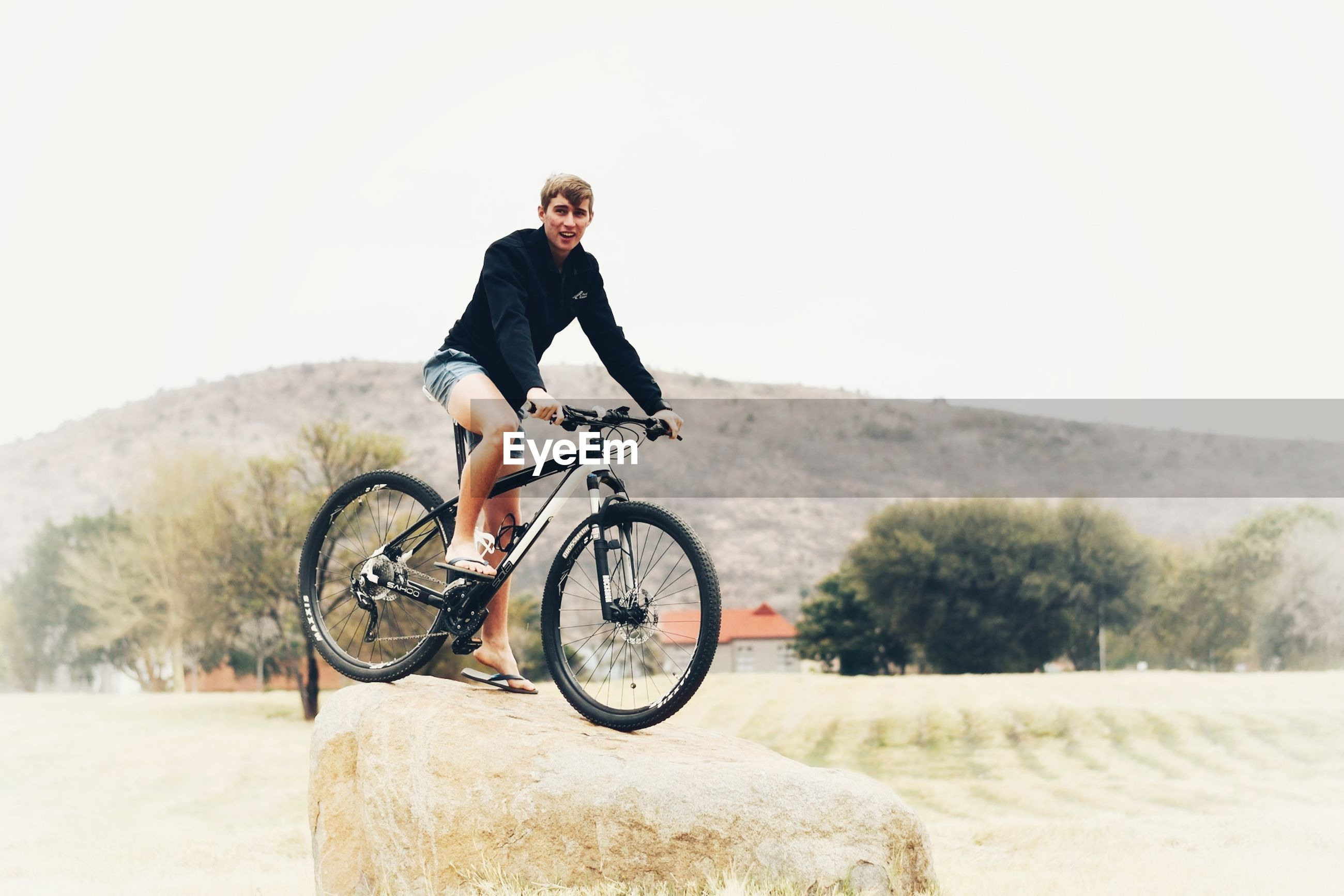 FULL LENGTH OF MAN RIDING BICYCLE ON ROAD