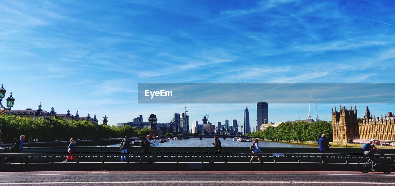 sky, architecture, built structure, building exterior, city, group of people, sport, nature, day, men, real people, cloud - sky, people, building, skyscraper, office building exterior, track and field, outdoors, urban skyline, incidental people