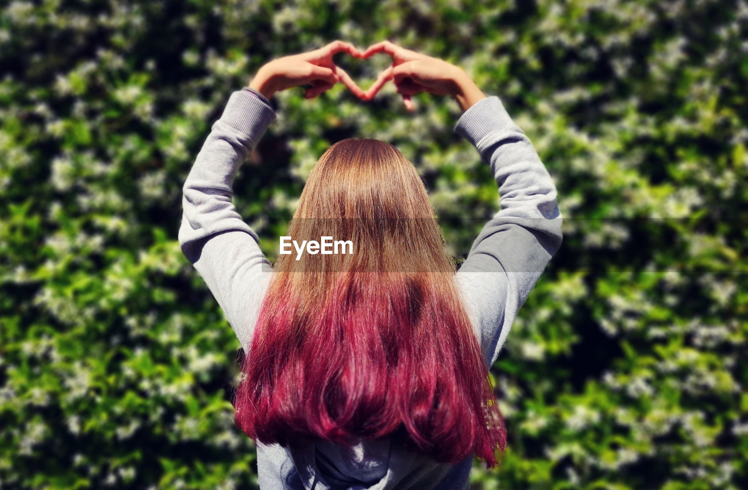 Rear view of woman with dyed hair making heart shape in park