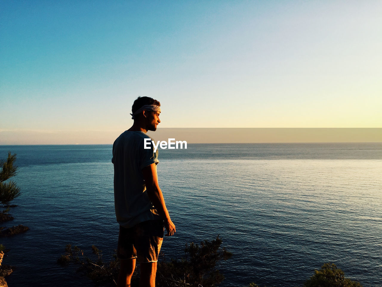 sky, sea, water, scenics - nature, beauty in nature, one person, lifestyles, standing, real people, sunset, leisure activity, tranquility, young adult, three quarter length, tranquil scene, non-urban scene, young men, casual clothing, copy space, horizon over water, outdoors, looking at view