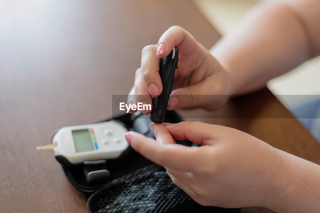 human body part, human hand, holding, real people, hand, technology, indoors, mobile phone, one person, women, body part, table, wireless technology, connection, lifestyles, adult, using phone, smart phone, human finger, finger, nail