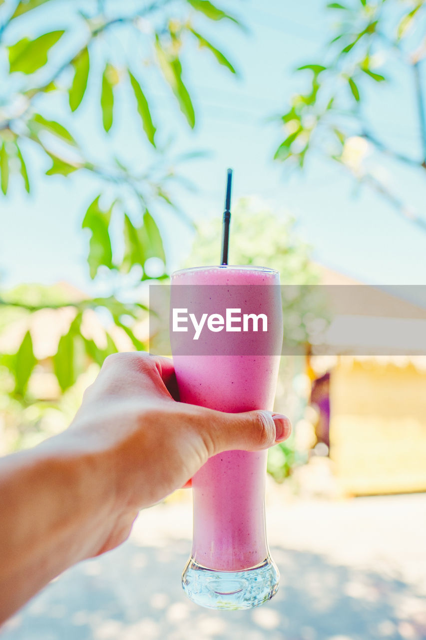 human hand, hand, human body part, one person, refreshment, food and drink, real people, holding, drink, food, drinking straw, straw, sweet food, close-up, focus on foreground, dairy product, day, ice cream, body part, sweet, pink color, finger, glass, outdoors, temptation, ice