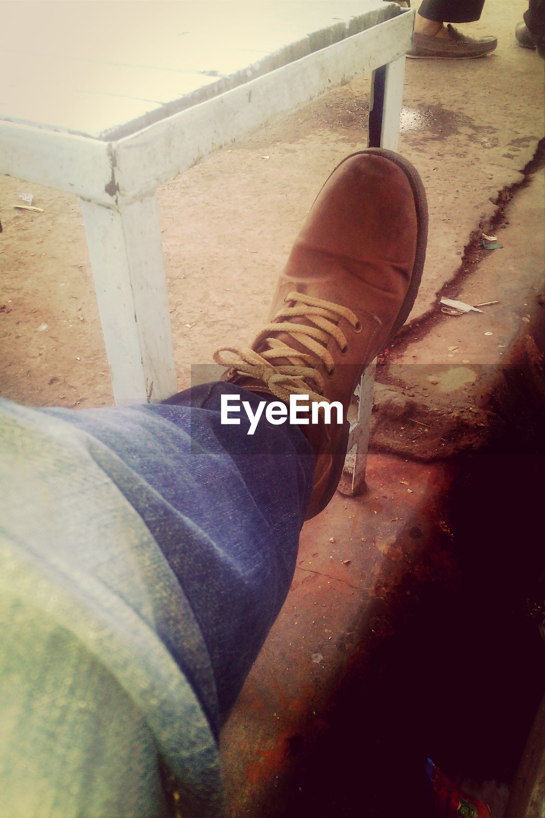 low section, shoe, person, personal perspective, high angle view, jeans, footwear, human foot, lifestyles, sunlight, standing, day, abandoned, outdoors, close-up, part of, old