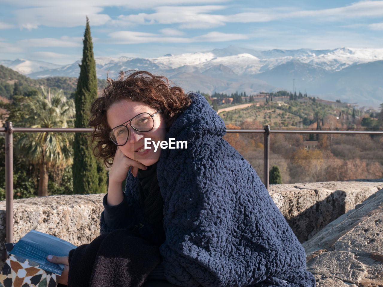 one person, glasses, sitting, lifestyles, mountain, smiling, young adult, real people, young women, leisure activity, portrait, nature, looking at camera, casual clothing, women, happiness, three quarter length, adult, eyeglasses, mountain range, hairstyle, hair, fashion, beautiful woman, outdoors