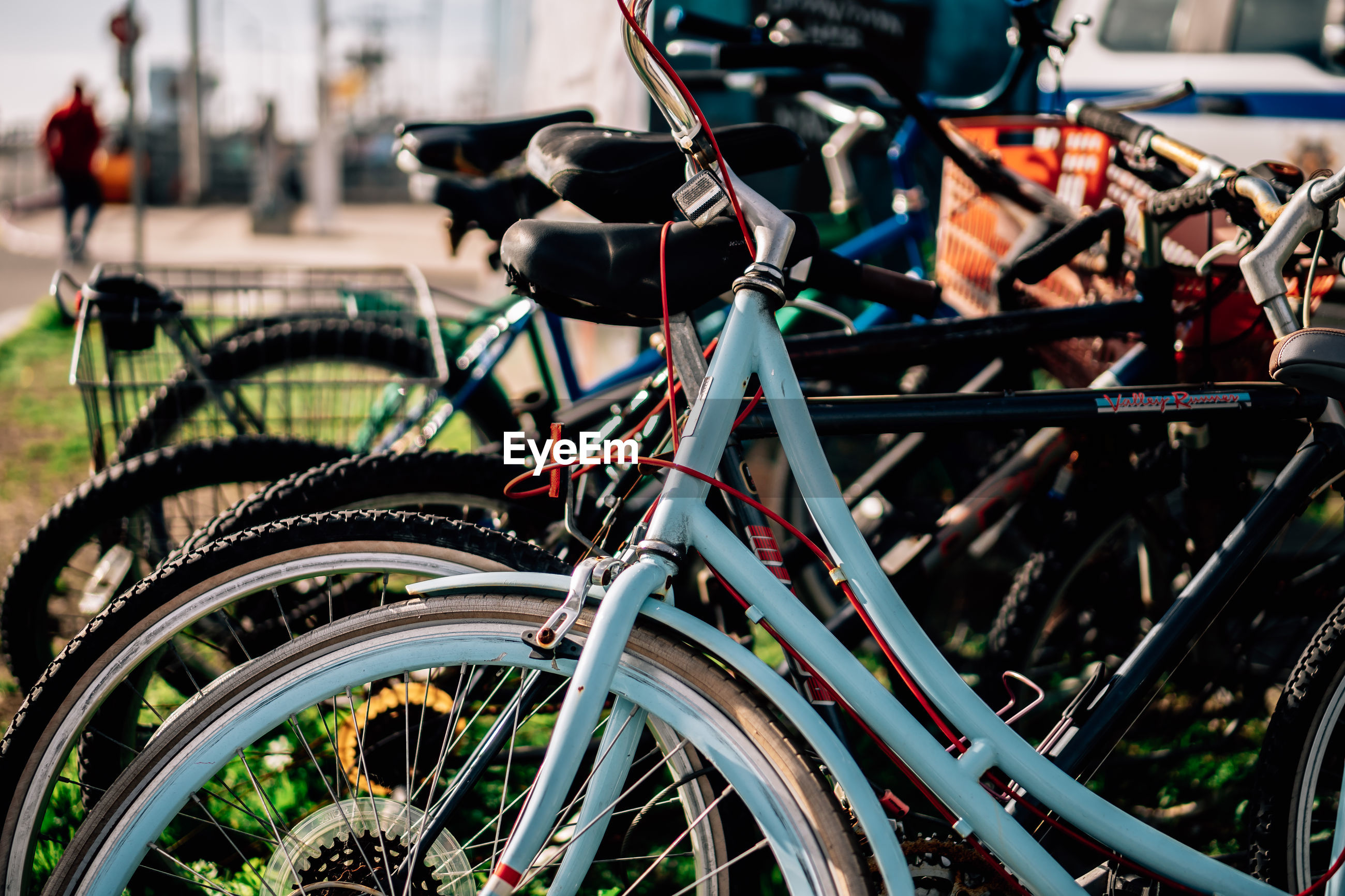 CLOSE-UP OF BICYCLE PARKED IN ROW AGAINST CITY
