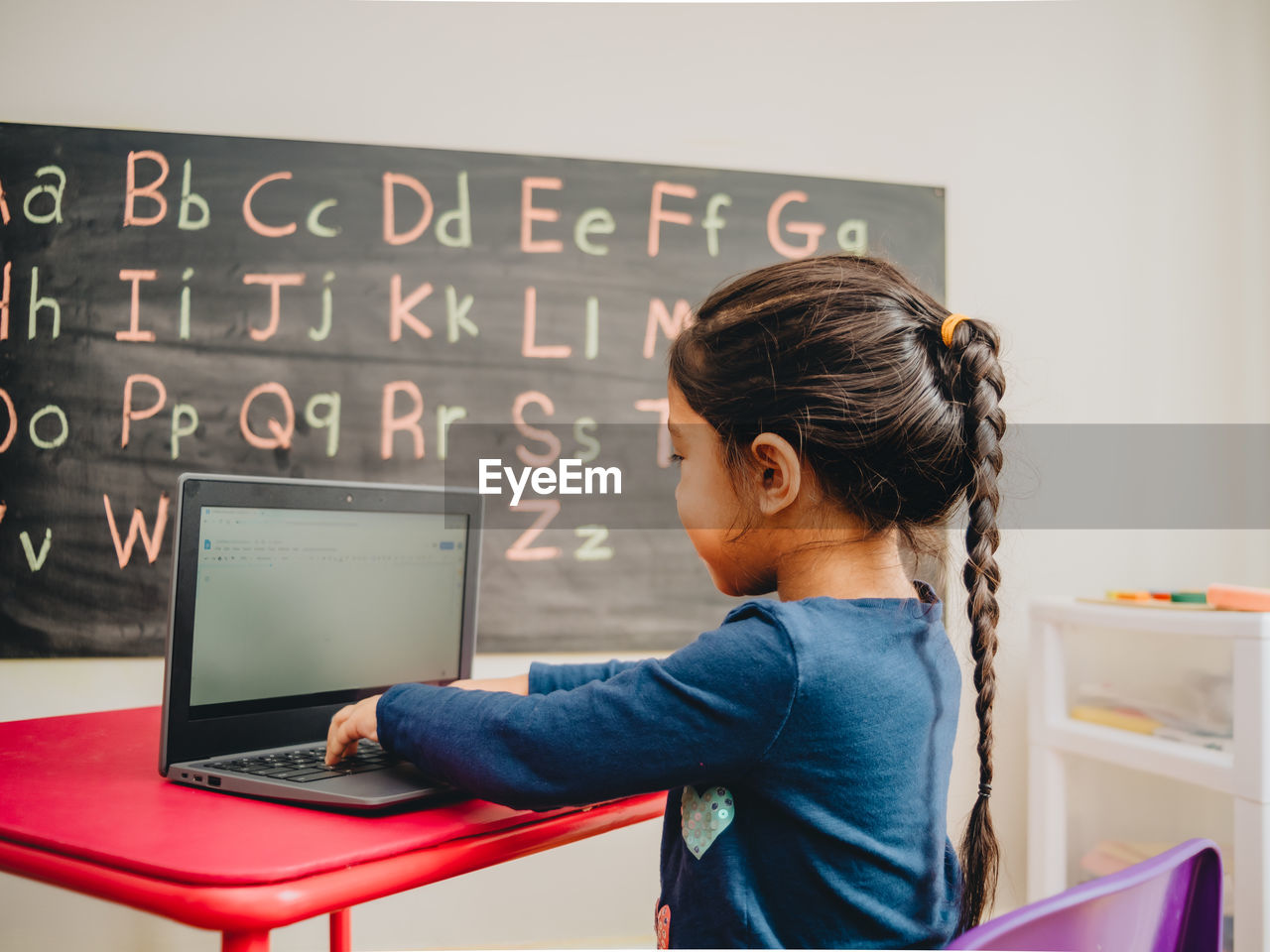 Side view of girl using laptop on table against blackboard