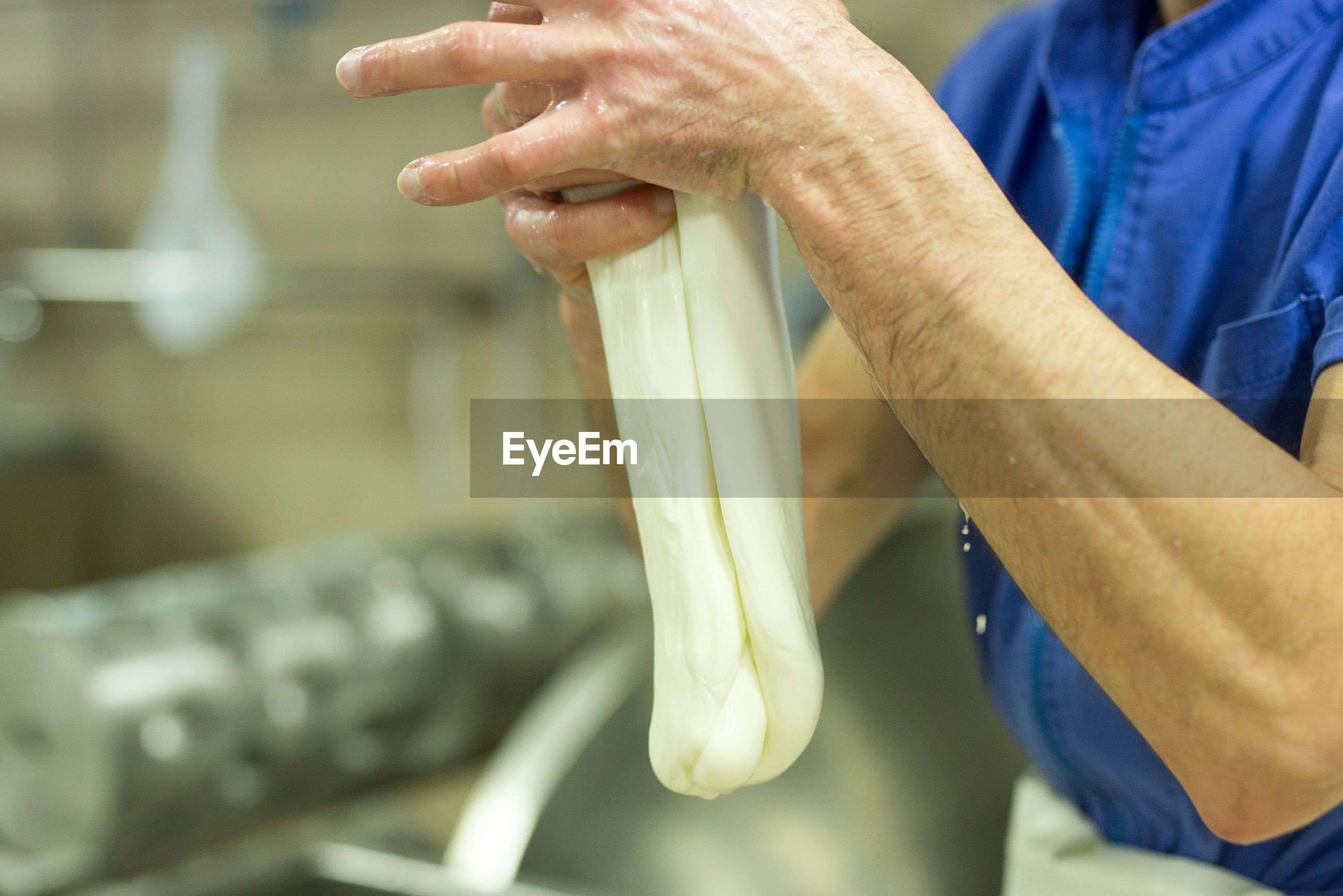 Midsection of man preparing mozzarella cheese in factory