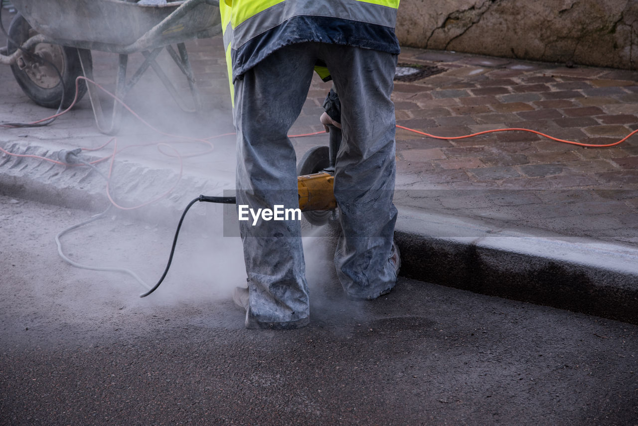 Low section of construction worker working on street