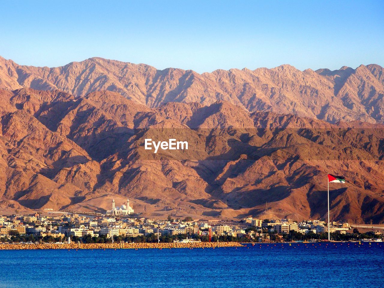 Jordanian Flag In City By Sea Against Mountains