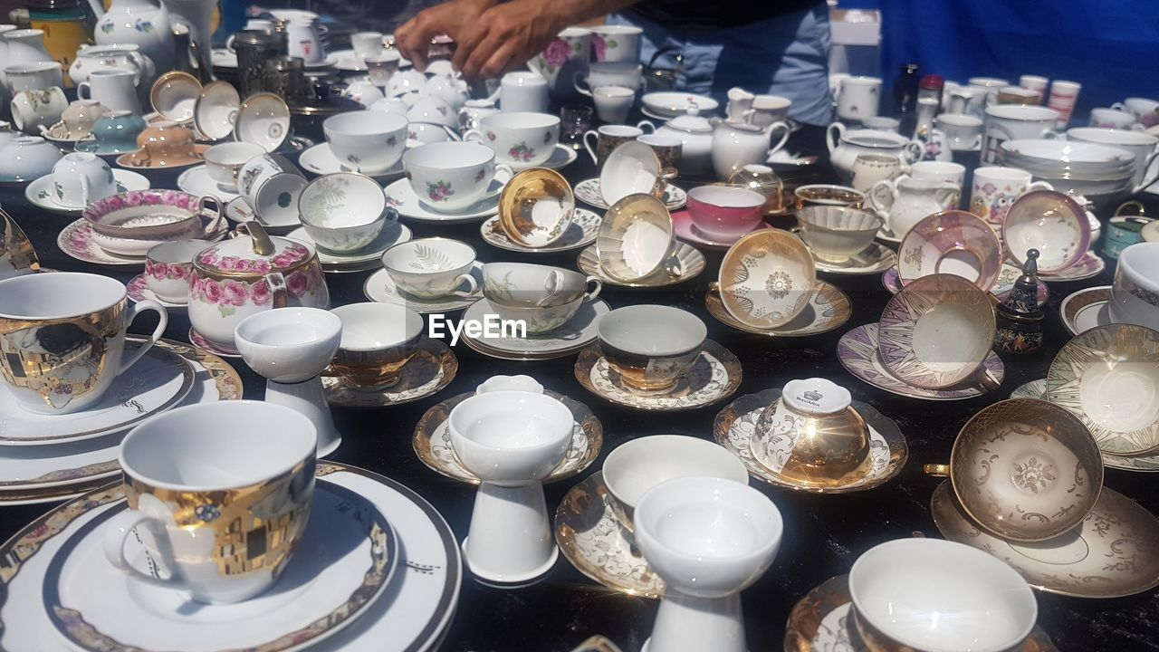 large group of objects, real people, abundance, hand, market, one person, retail, human hand, choice, for sale, household equipment, high angle view, food and drink, market stall, variation, metal, arrangement, container, close-up, kitchen utensil, crockery, antique, retail display