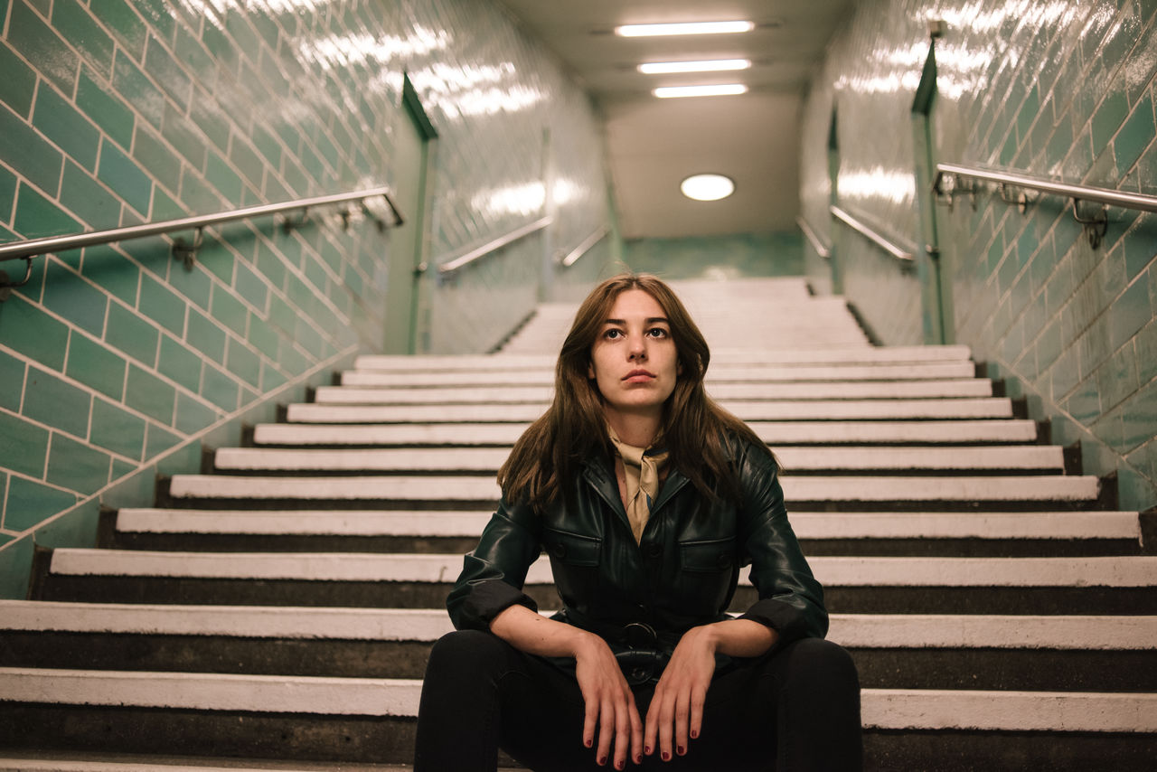 Thoughtful young woman sitting on steps at subway station