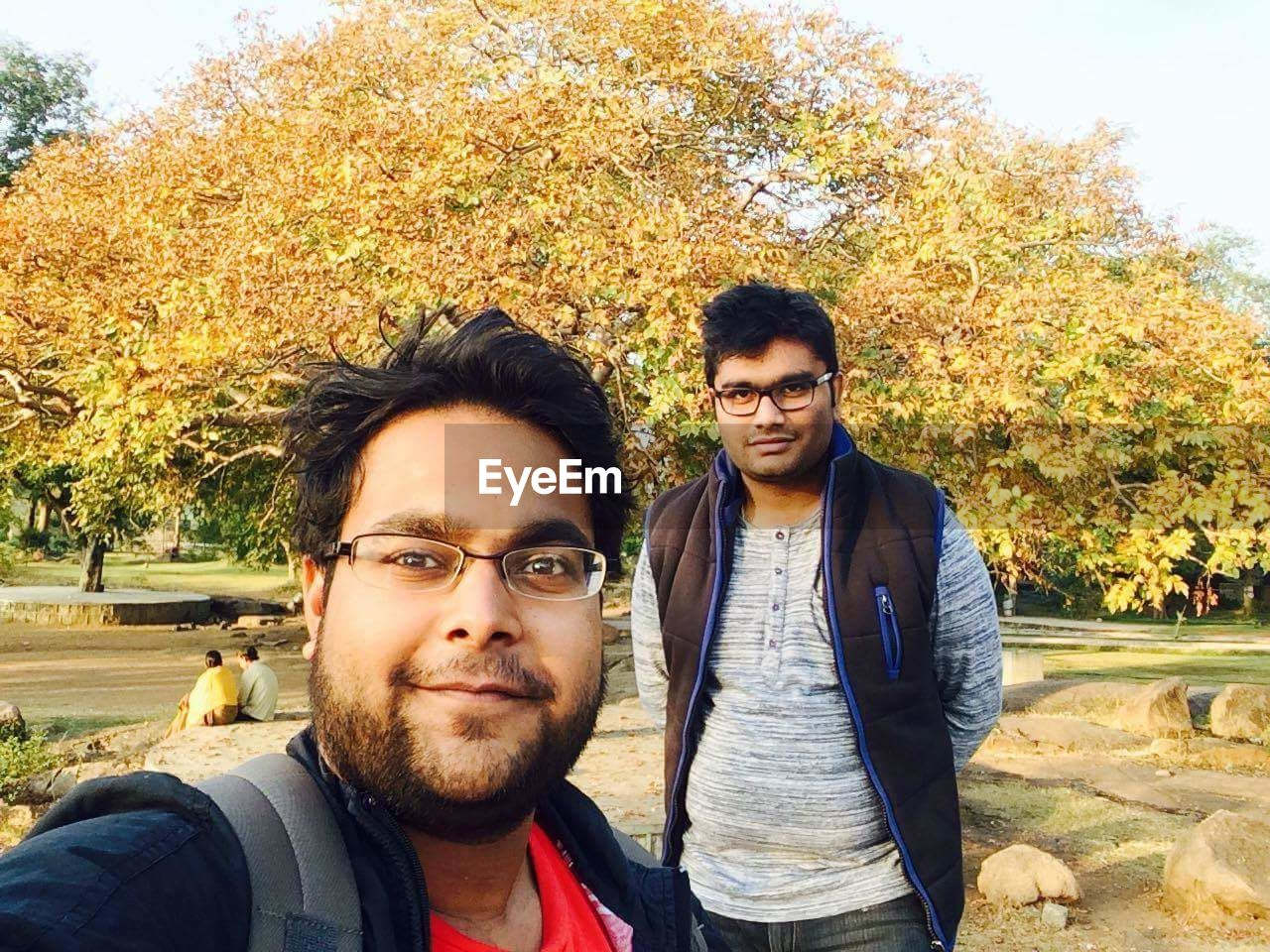 looking at camera, portrait, young men, real people, young adult, front view, two people, togetherness, mid adult men, casual clothing, lifestyles, leisure activity, day, tree, young women, mid adult, smiling, outdoors, love, bonding, autumn, park - man made space, beard, happiness, couple - relationship, standing, nature, people