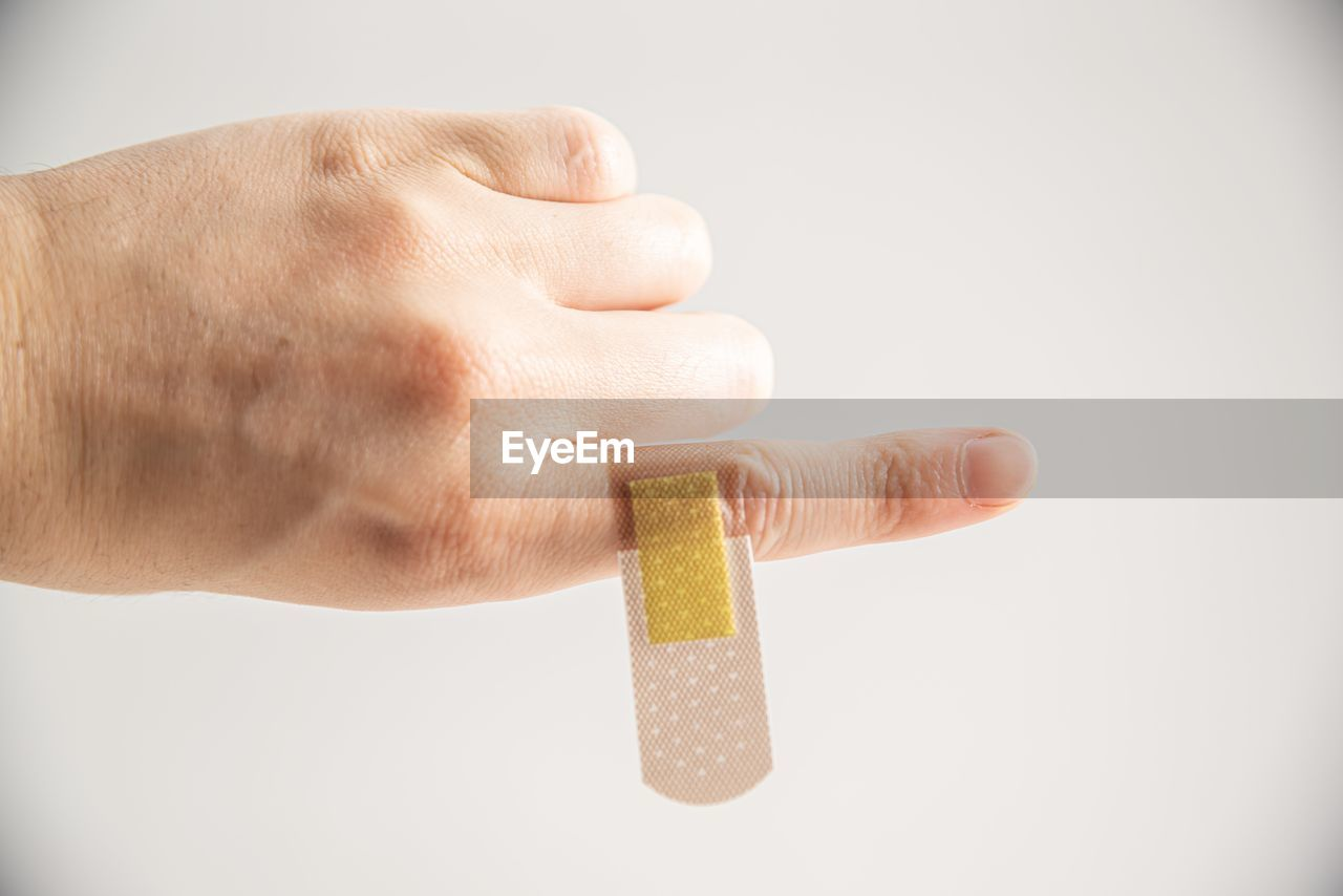 human hand, human body part, hand, finger, one person, human finger, body part, holding, studio shot, indoors, close-up, white background, food, food and drink, unrecognizable person, real people, lifestyles, men, copy space, temptation