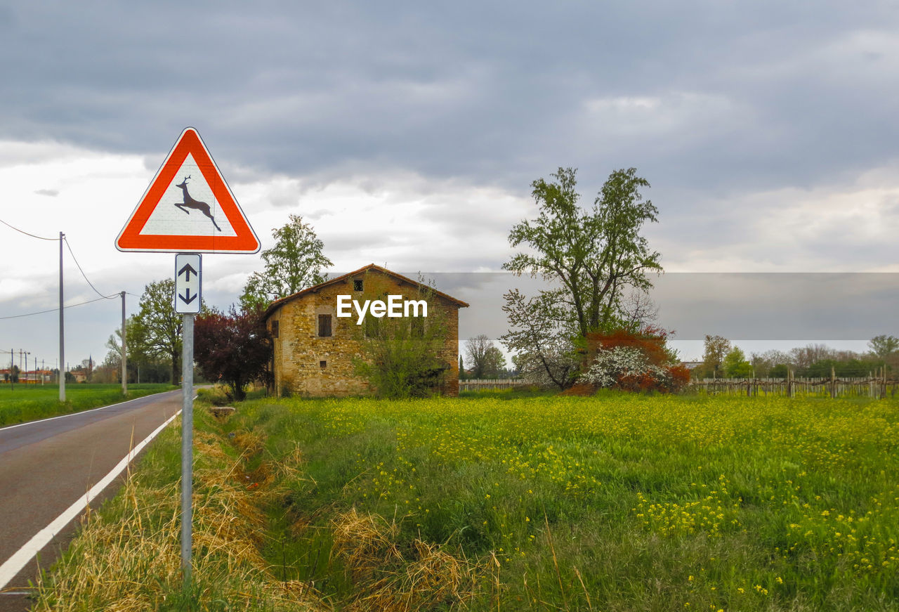 sign, plant, grass, sky, nature, cloud - sky, built structure, warning sign, tree, road, architecture, communication, road sign, triangle shape, field, land, no people, day, transportation, building, outdoors