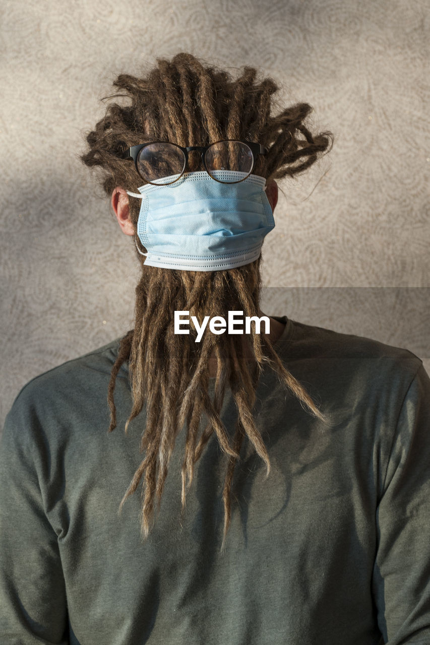 Woman wearing mask with dreadlocks against wall