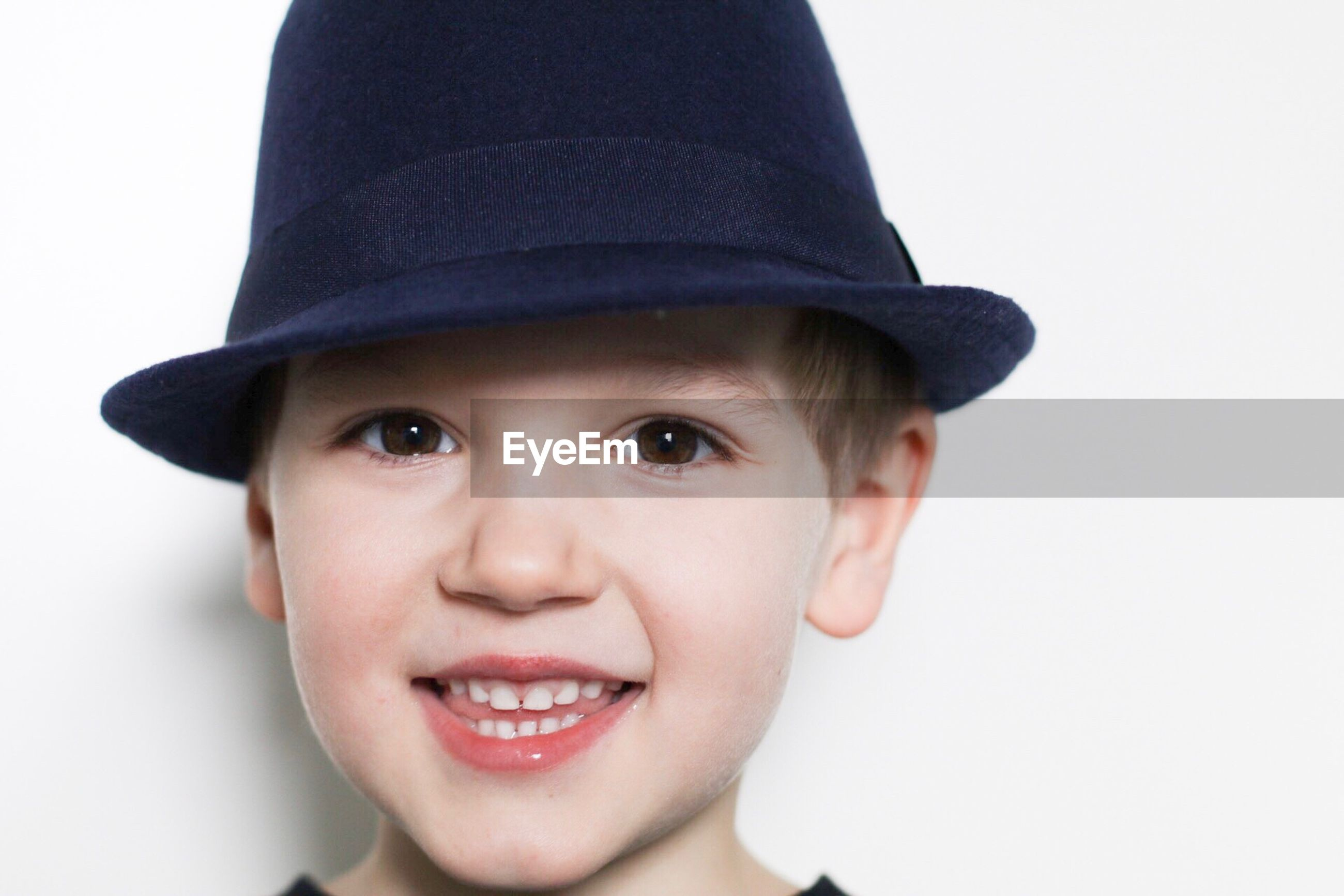 Close-up portrait of smiling boy wearing hat against white wall