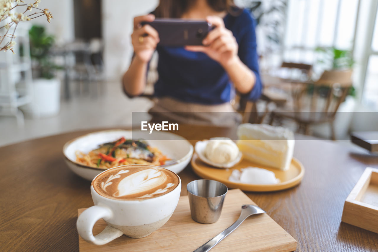 Midsection Of Woman Photographing Food Using Phone