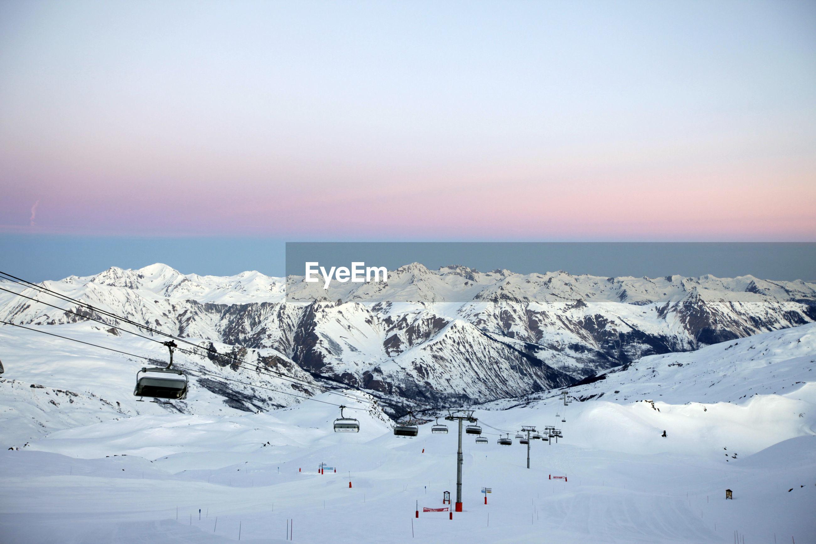 Ski lift on snow covered landscape during sunset