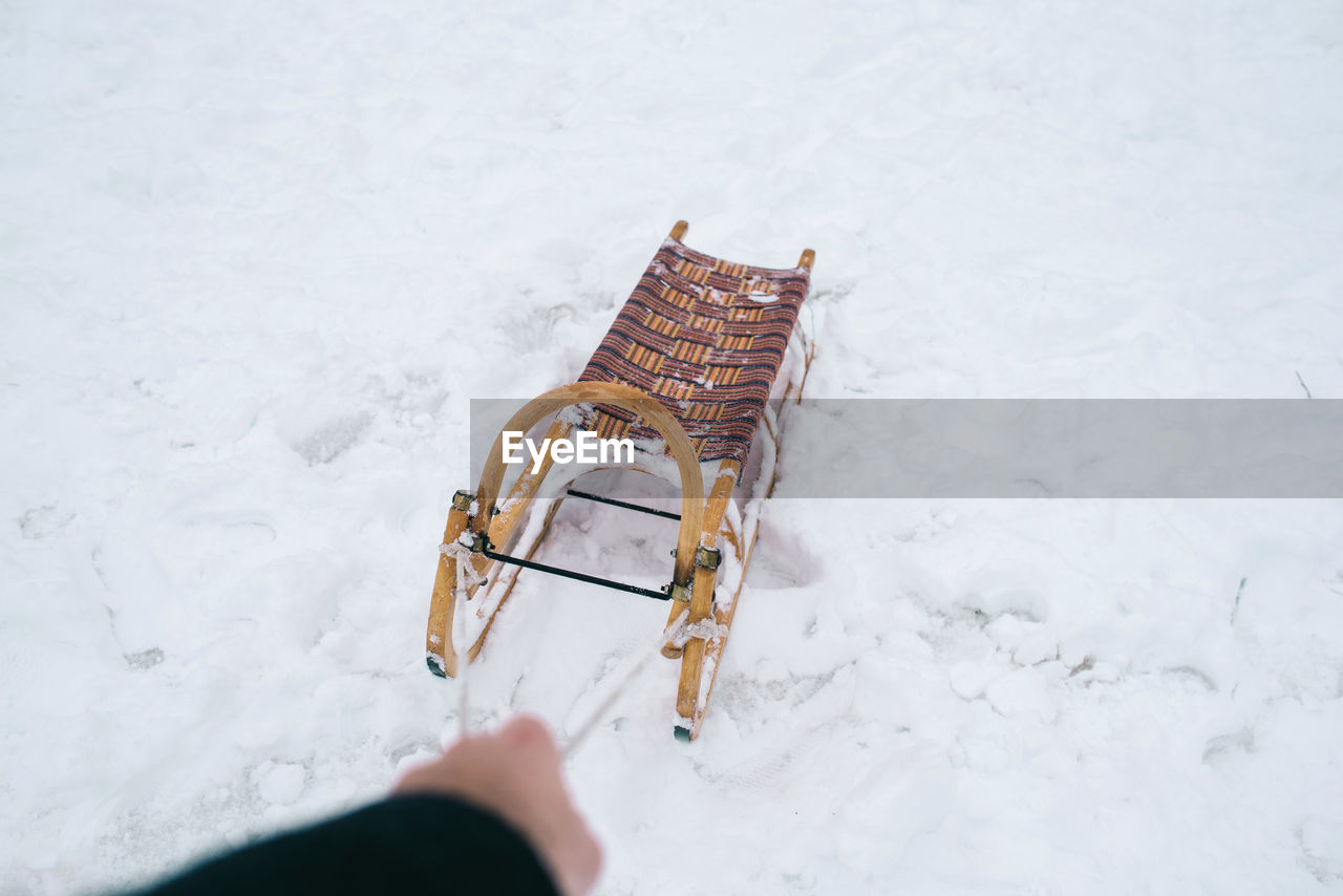Cropped hand of person pulling sled on snow