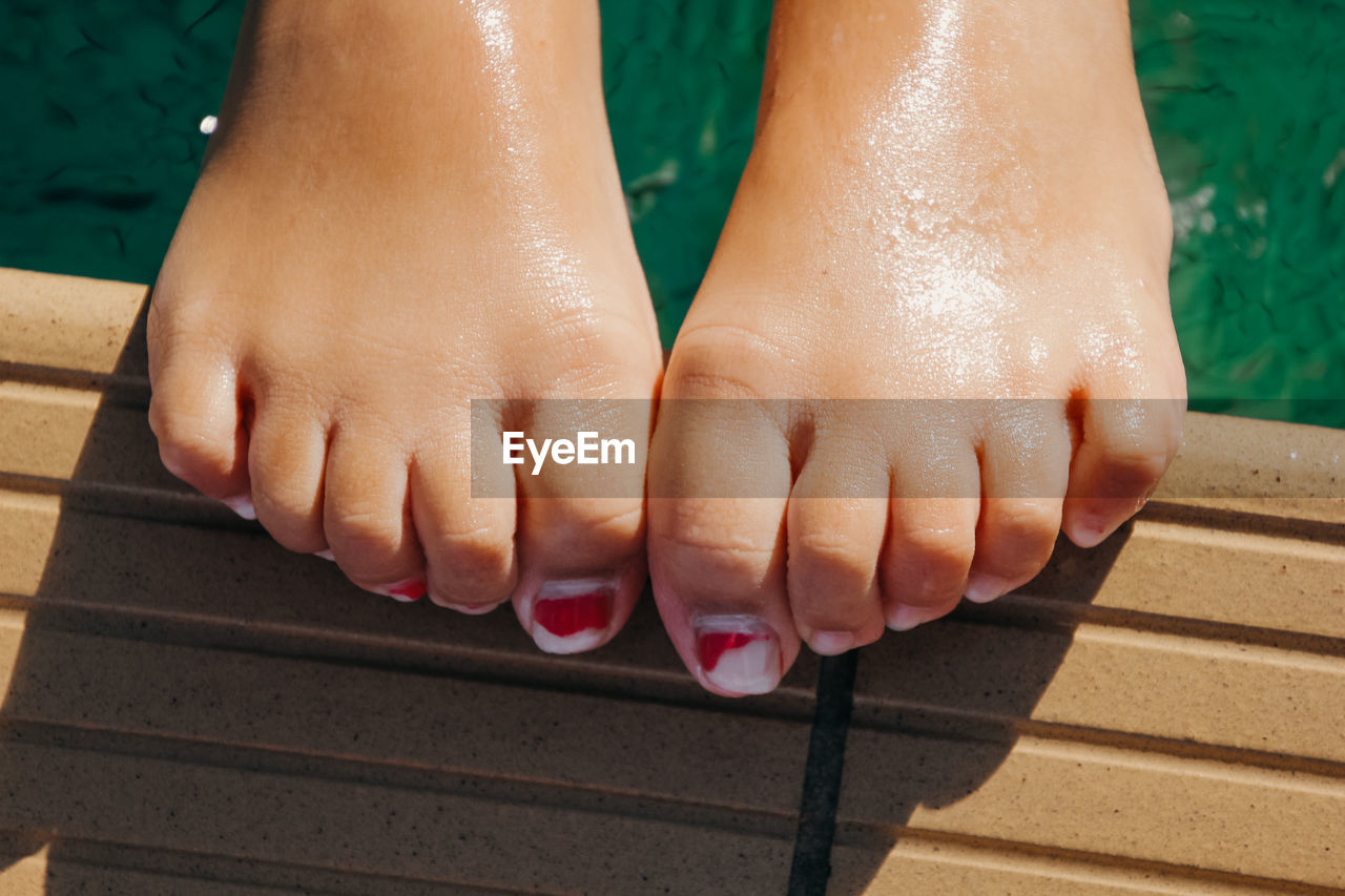 Close-up of woman legs at the edge of pool