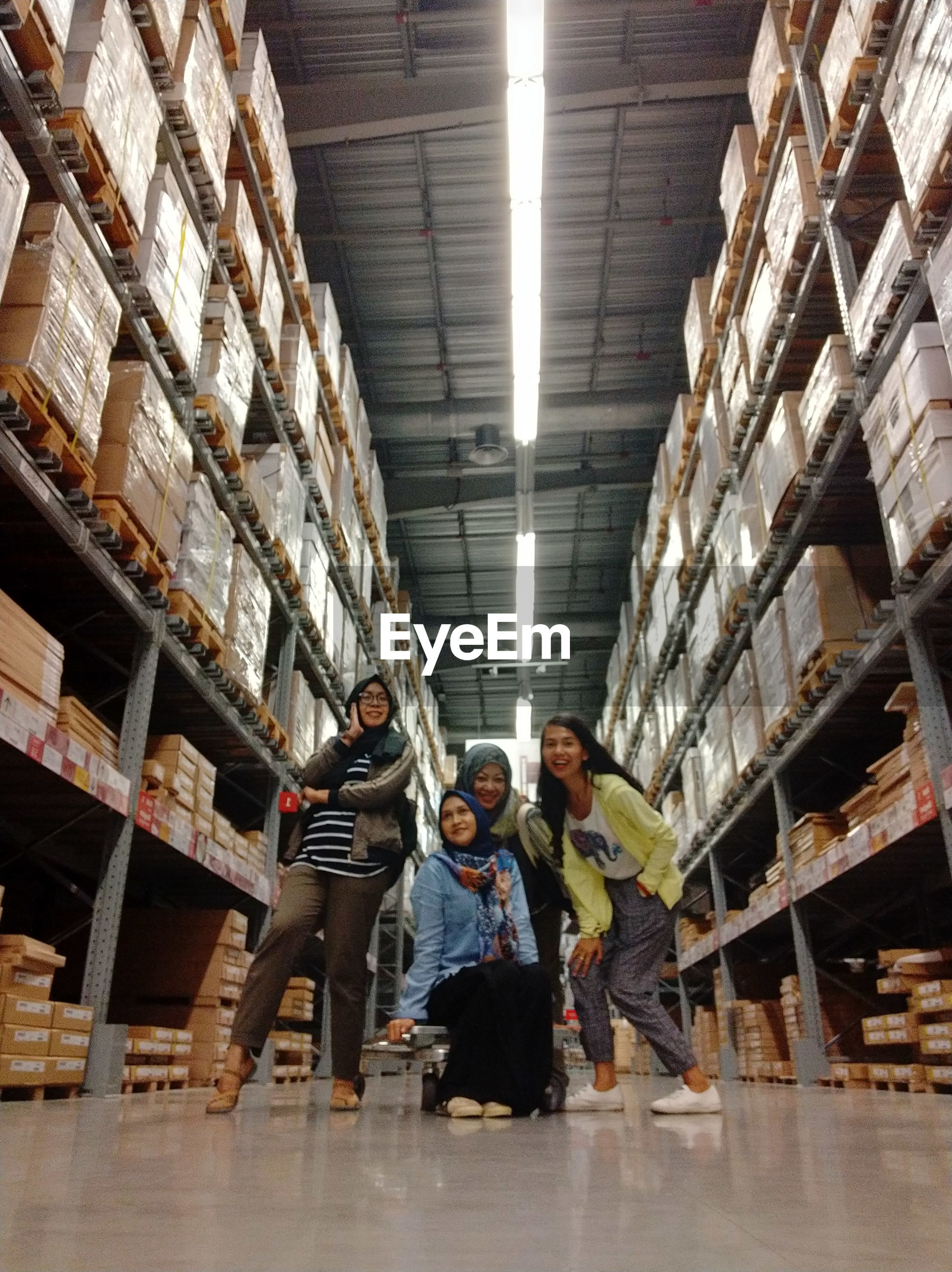 Low angle portrait of happy friends posing in warehouse