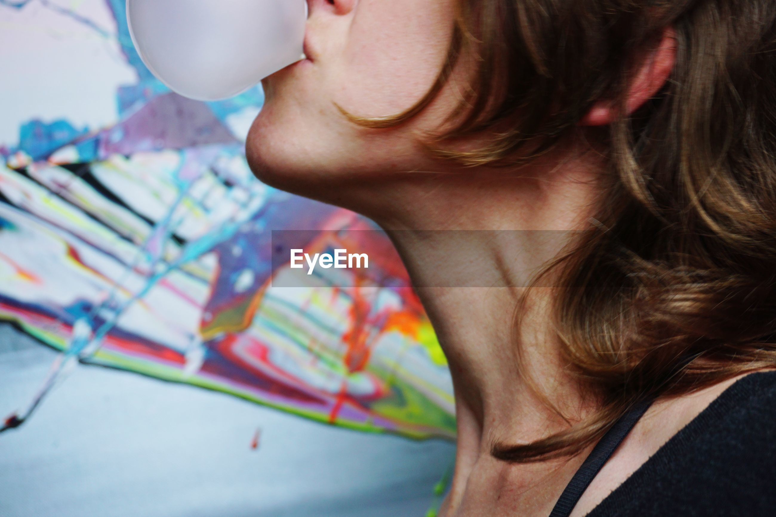 Close-up of woman blowing bubble gum