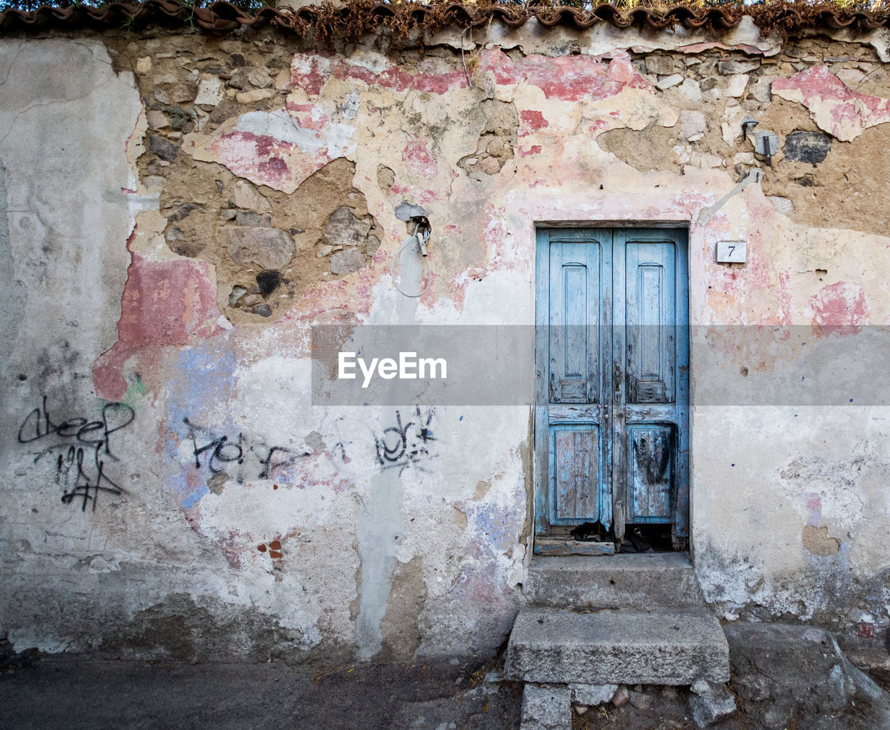 architecture, built structure, building, building exterior, old, wall - building feature, no people, door, abandoned, entrance, weathered, day, damaged, house, window, peeling off, graffiti, wall, run-down, peeled, outdoors, deterioration, ruined, plaster, messy, concrete