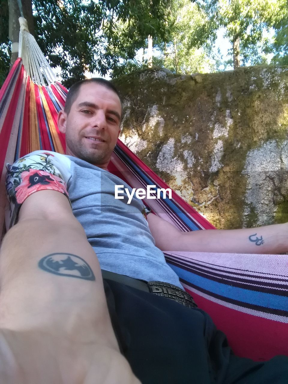 real people, leisure activity, lifestyles, one person, day, casual clothing, outdoors, young men, lying down, looking at camera, relaxation, tree, smiling, young adult, portrait, nature, people