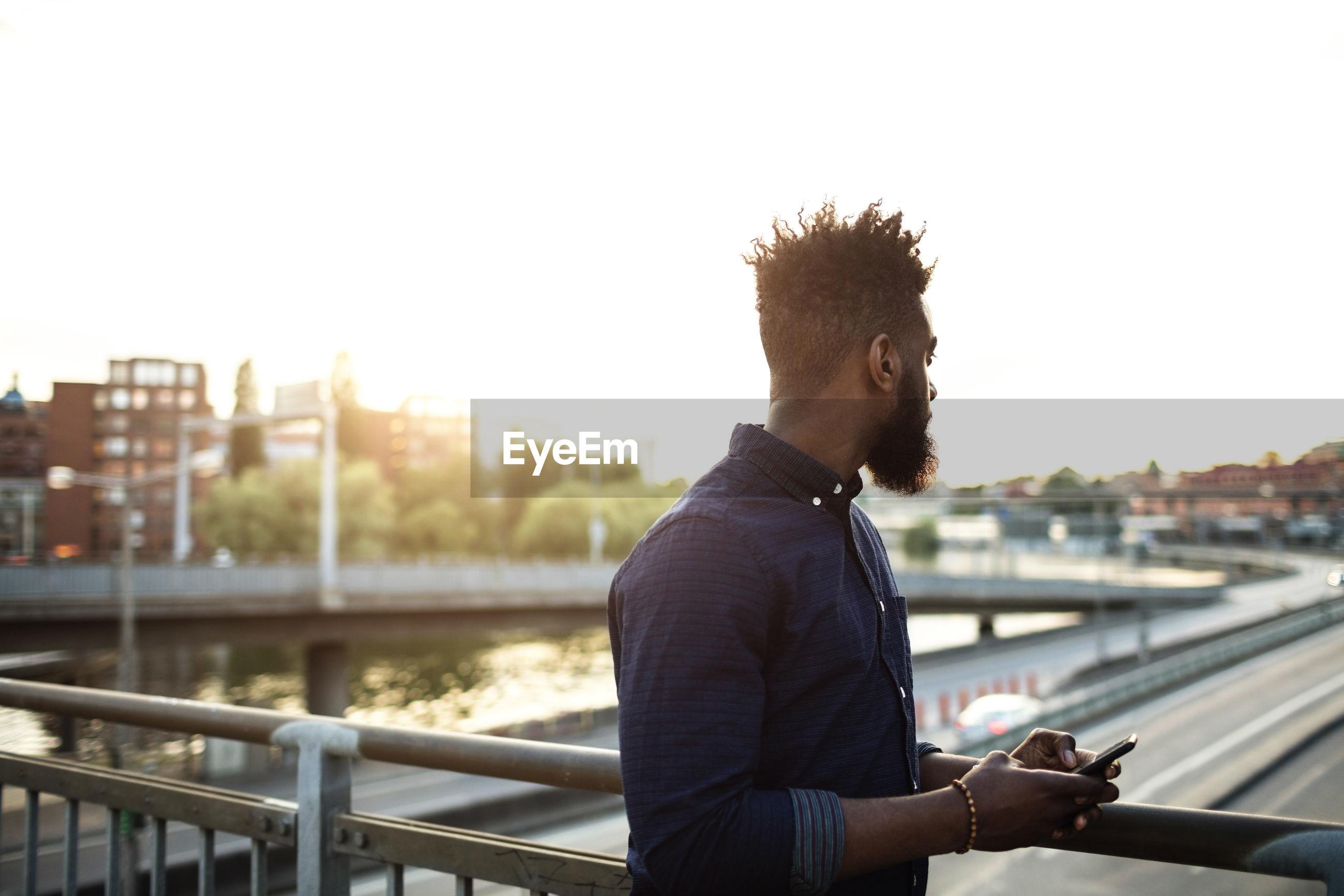 YOUNG MAN LOOKING AT CITY VIEW