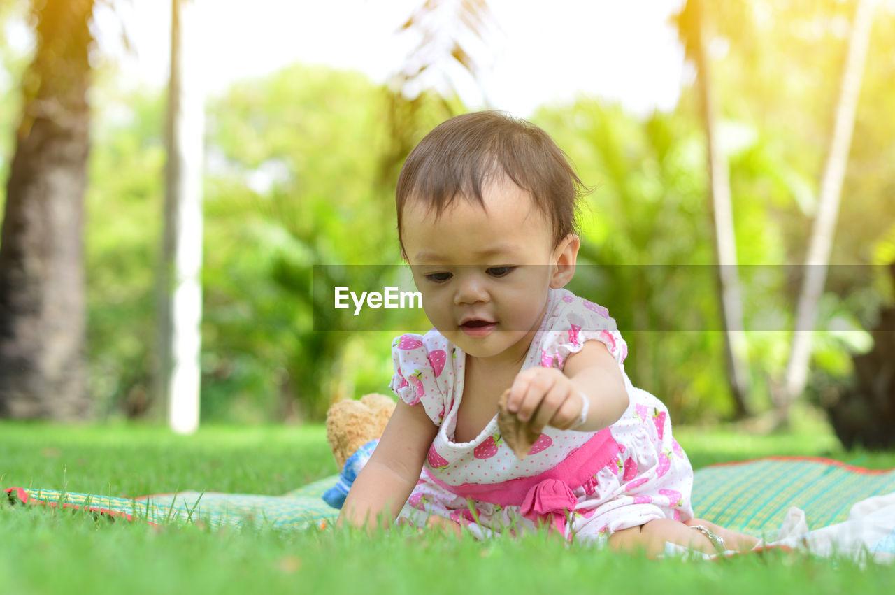 Baby girl on grassy field