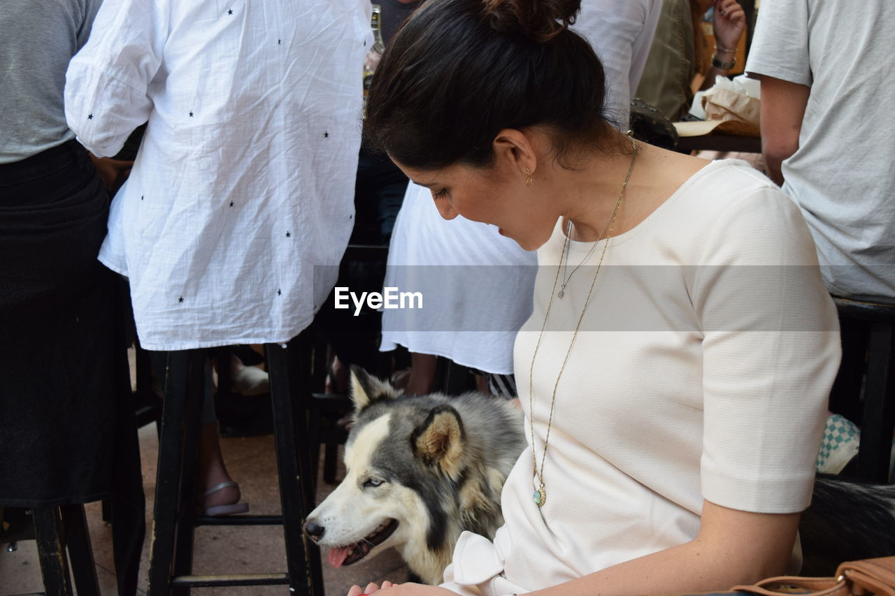 Young Woman Petting Dog While Sitting On Chair