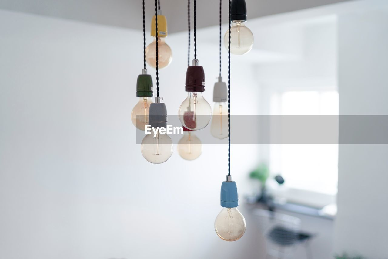 hanging, indoors, no people, decoration, focus on foreground, light bulb, lighting equipment, ceiling, close-up, low angle view, electricity, still life, wind chime, technology, string, healthcare and medicine, day, machinery, in a row, equipment, electrical equipment