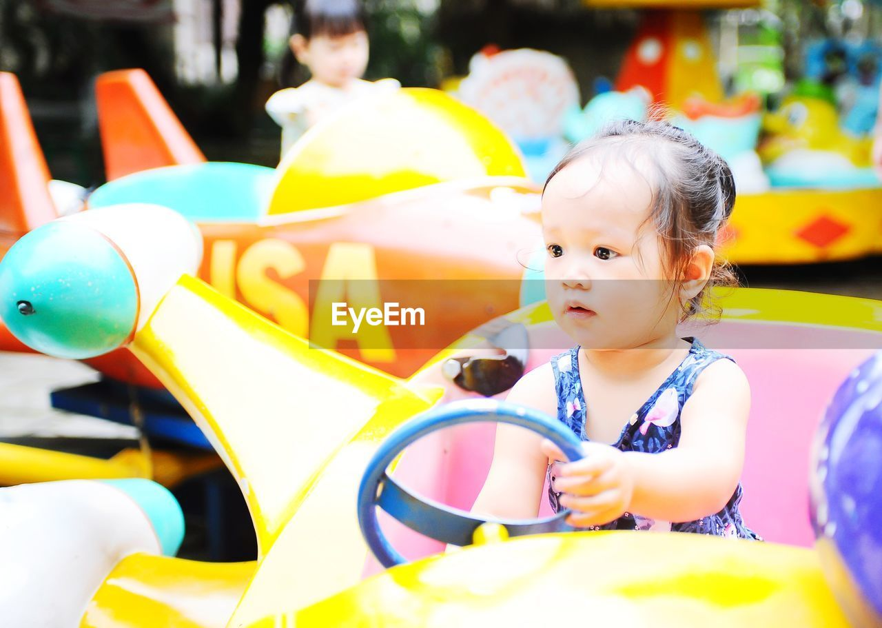 childhood, child, real people, incidental people, innocence, one person, cute, baby, lifestyles, day, young, amusement park, leisure activity, looking, focus on foreground, sitting, yellow, portrait, headshot, outdoor play equipment