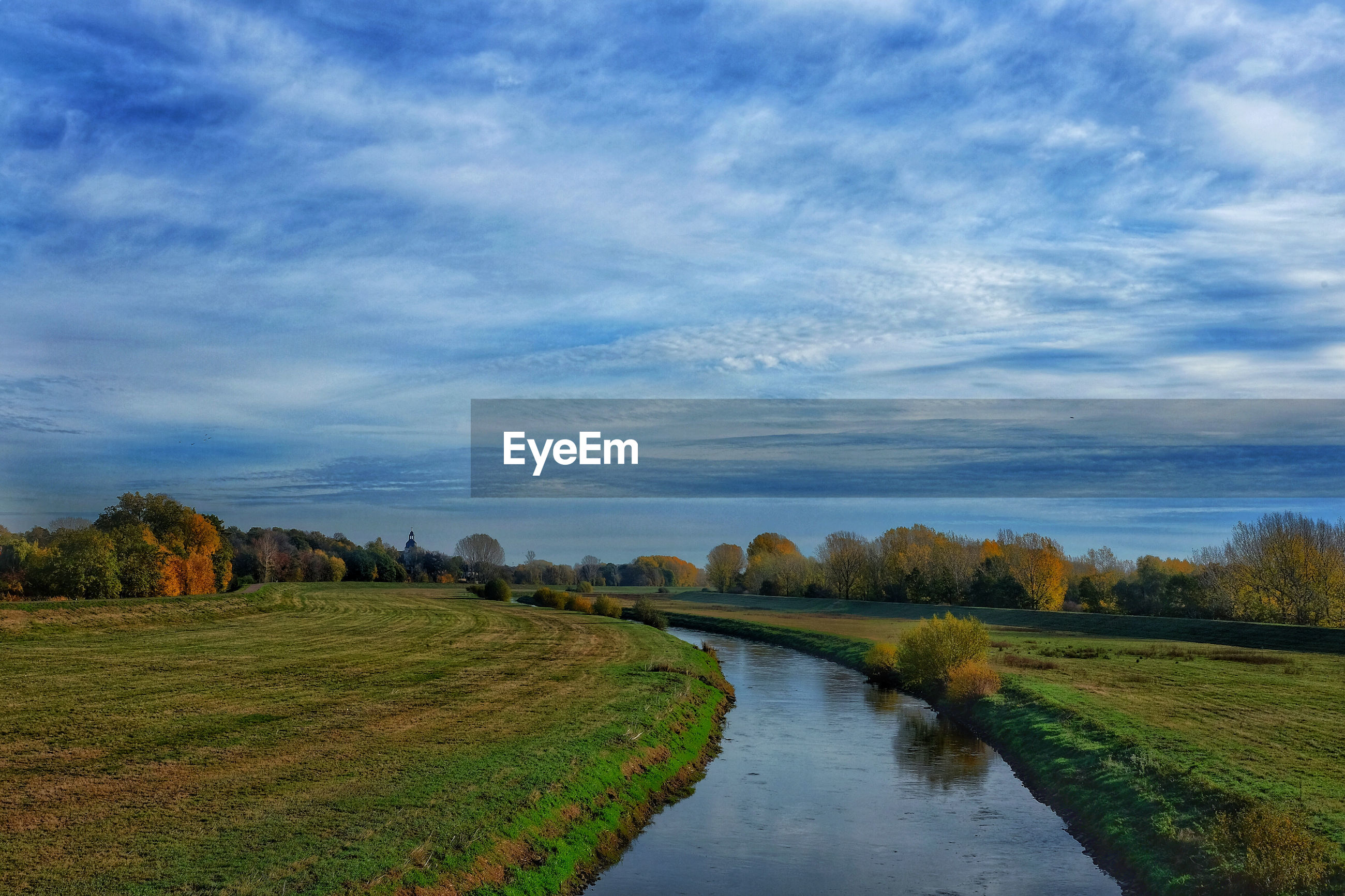 Scenic view of canal amidst field against sky