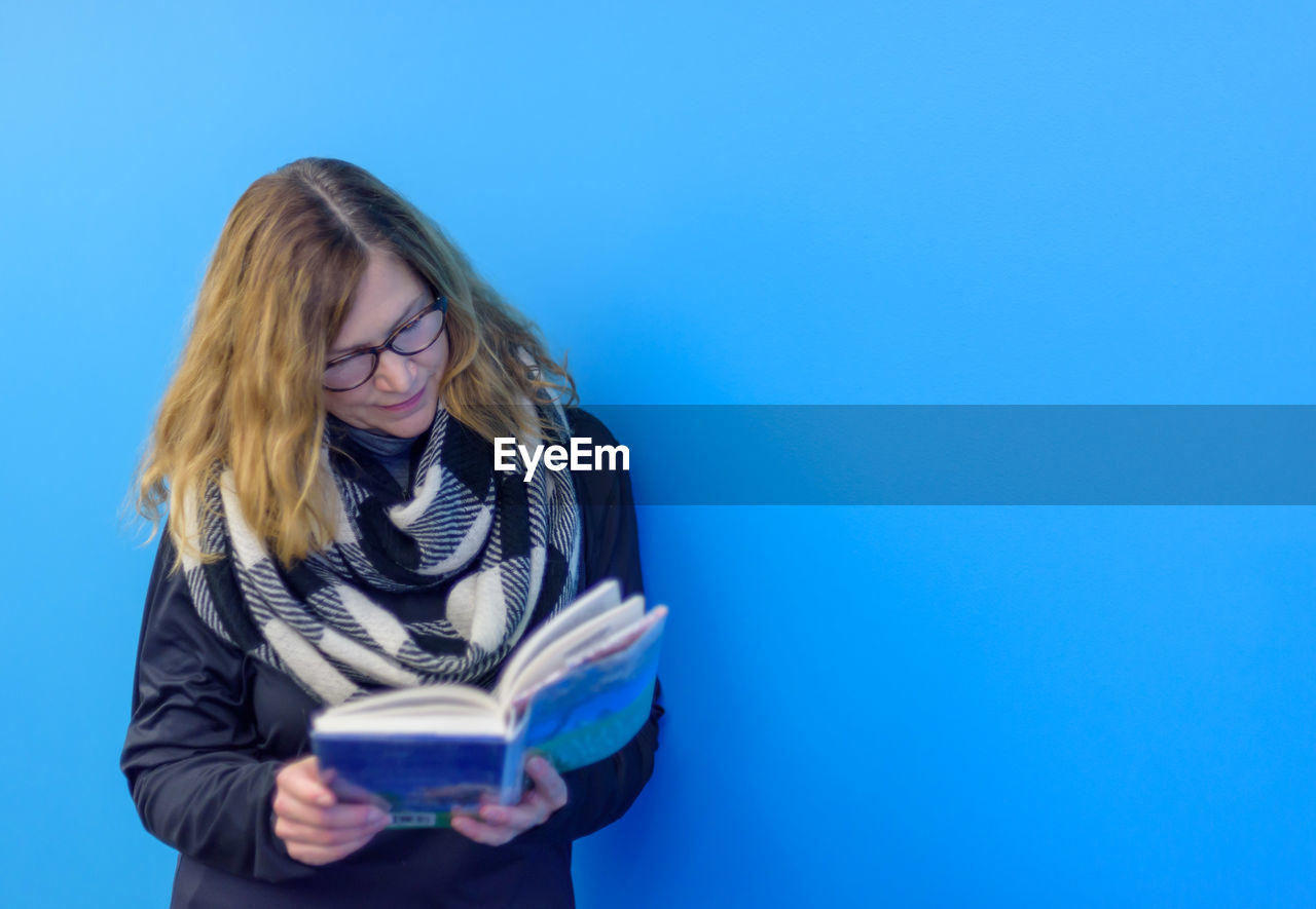 Mature woman reading book while standing against blue background