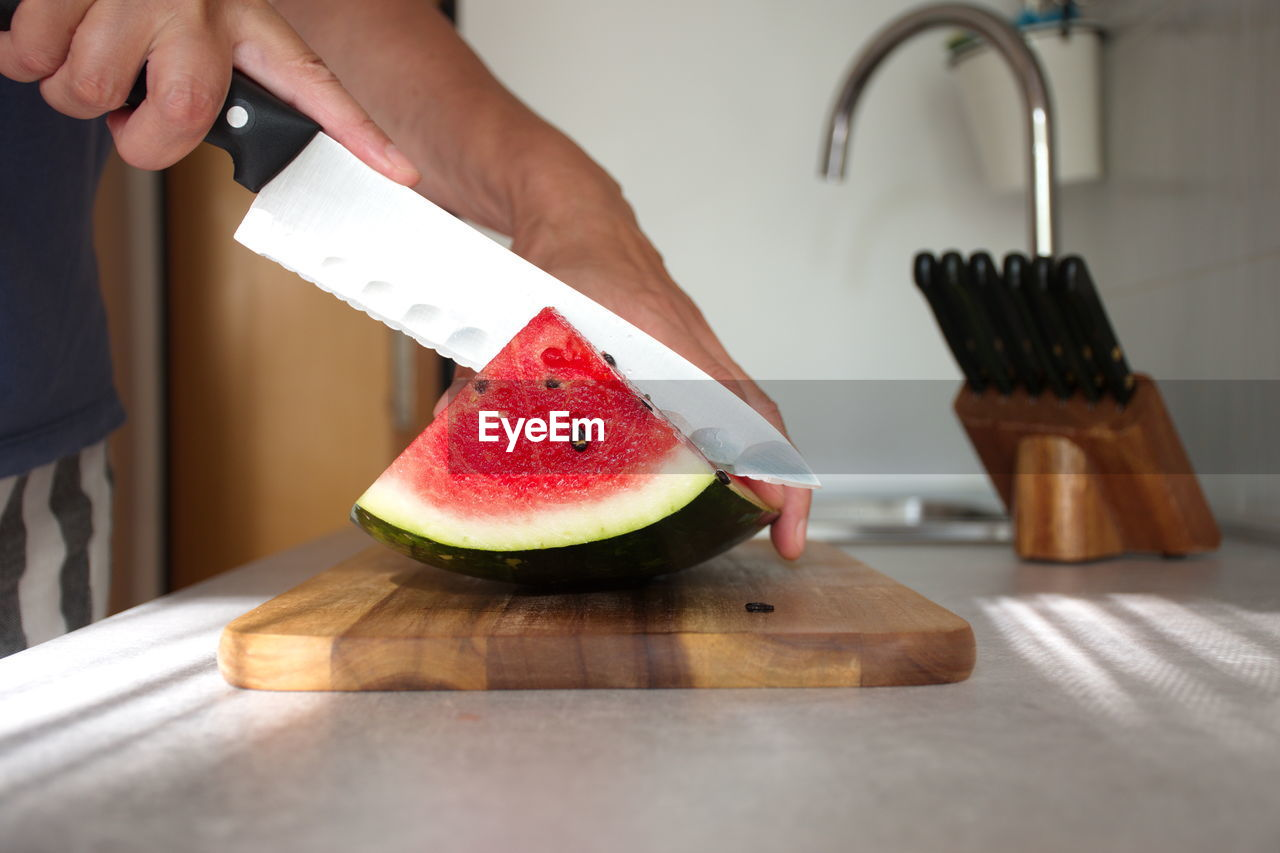 fruit, food, one person, human hand, healthy eating, food and drink, wellbeing, indoors, hand, freshness, human body part, real people, holding, slice, cutting board, watermelon, home, domestic kitchen, domestic room, kitchen, preparation, preparing food