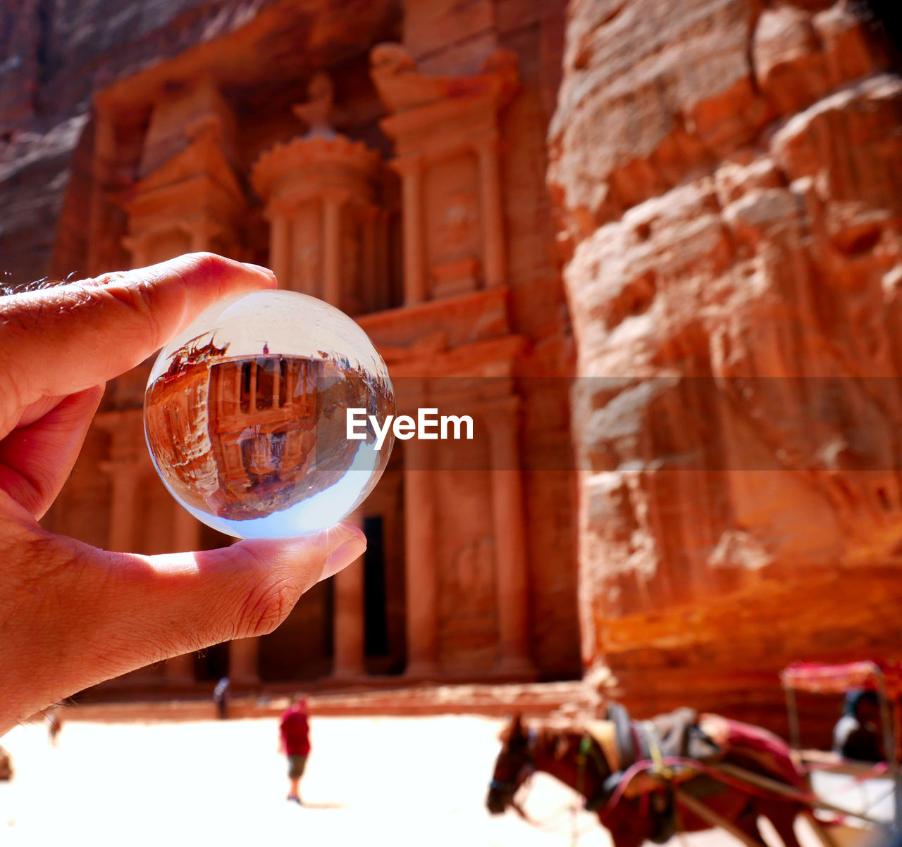 human hand, hand, holding, human body part, one person, focus on foreground, real people, unrecognizable person, built structure, sphere, architecture, lifestyles, crystal ball, human finger, finger, body part, day, building exterior, building, outdoors, glass, human limb
