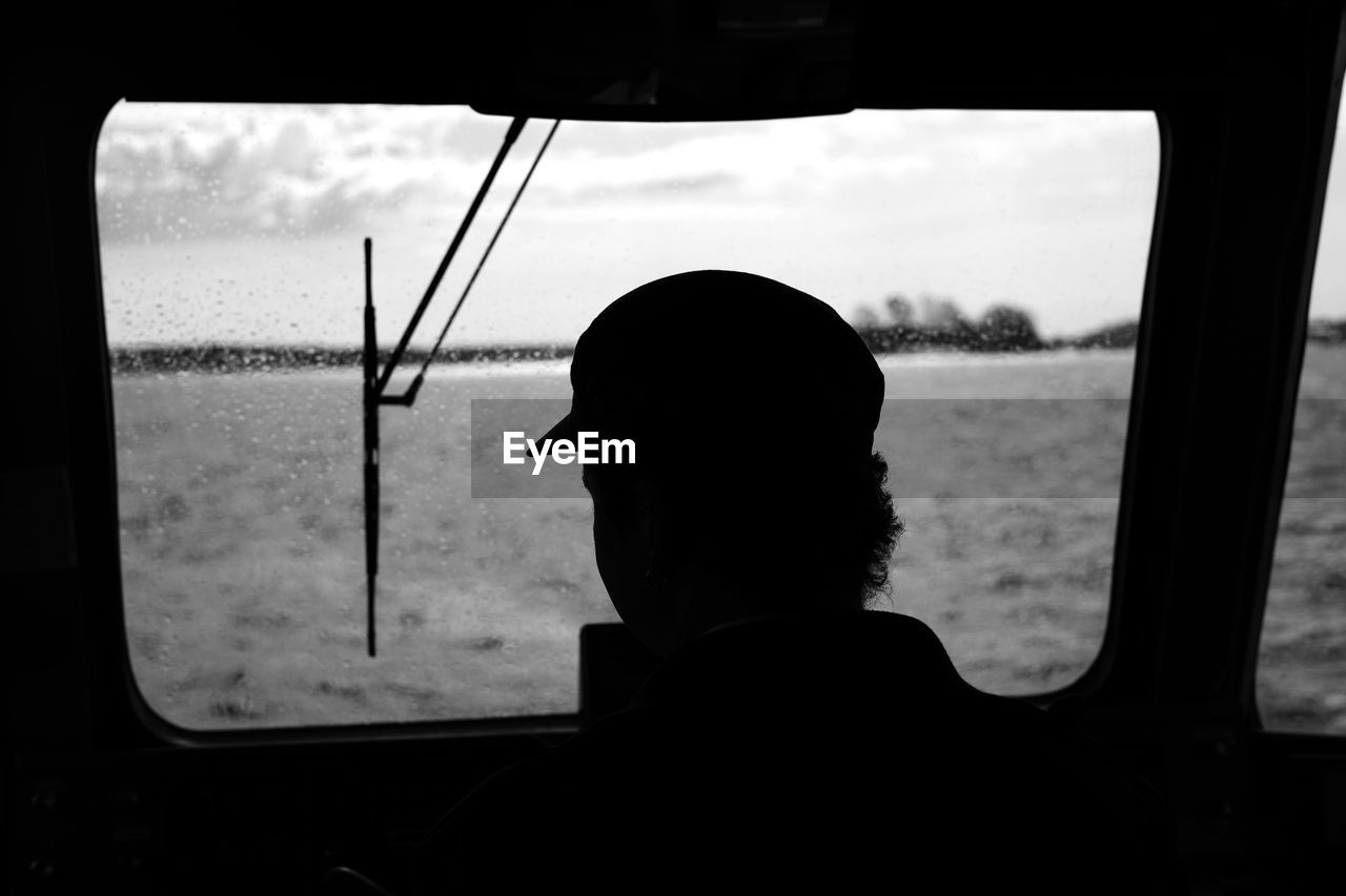 Rear View Of Silhouette Man Looking Through Window