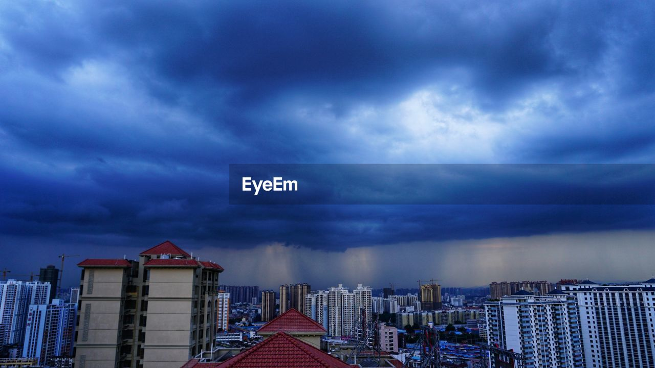 PANORAMIC VIEW OF BUILDINGS AGAINST DRAMATIC SKY