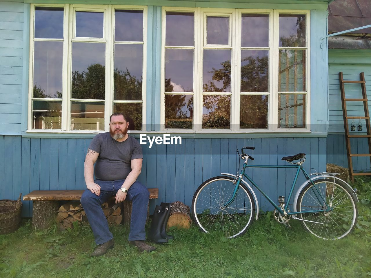 Portrait of man with bicycle against plants