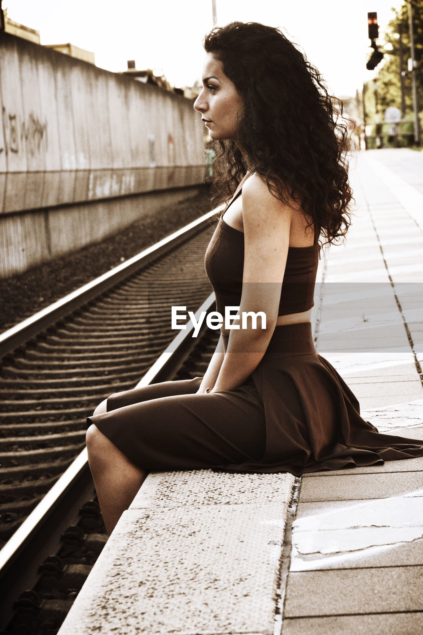 Side view of woman sitting on railroad station platform